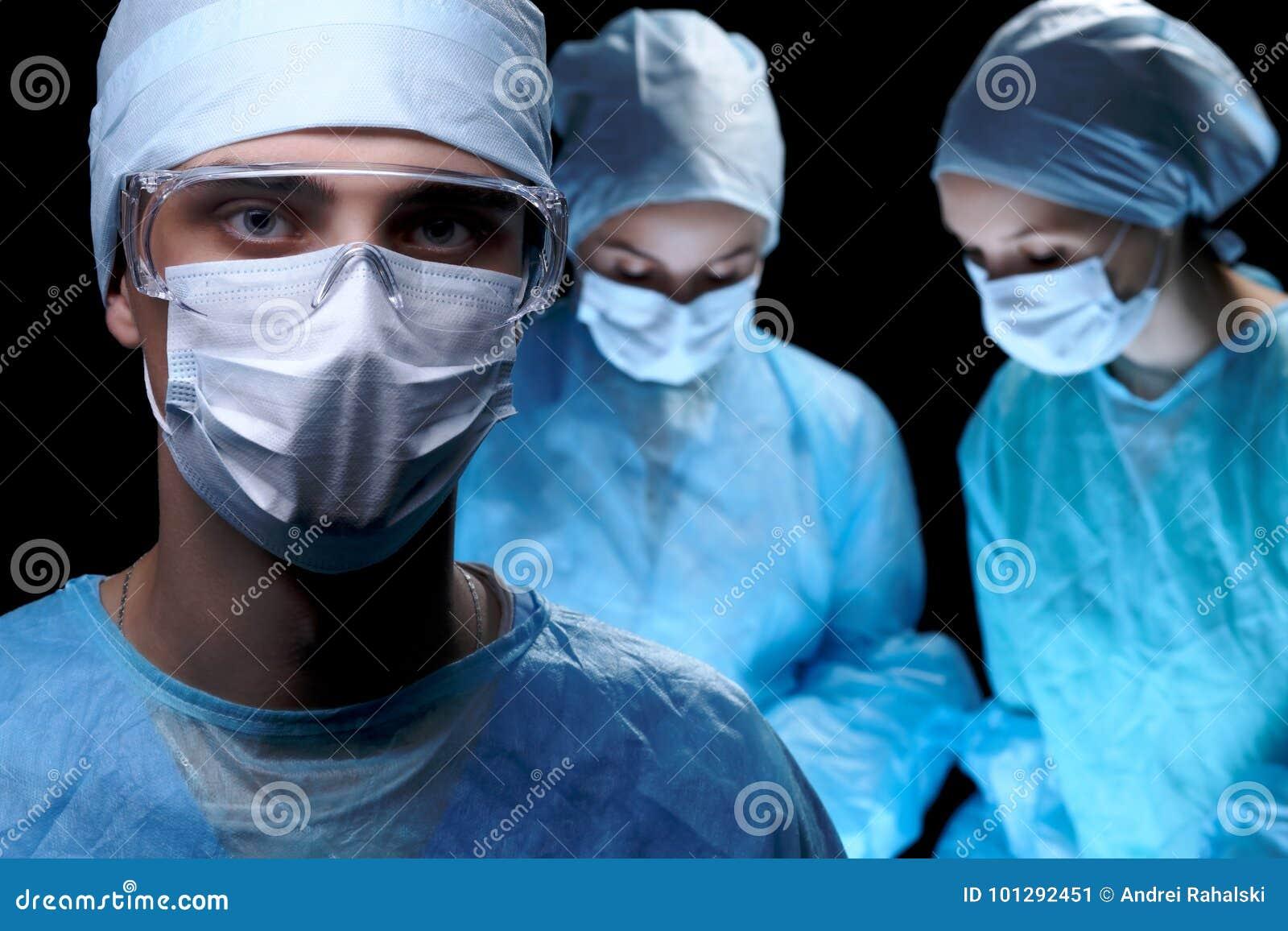 Equipa médica que executa a operação Foco no doutor masculino