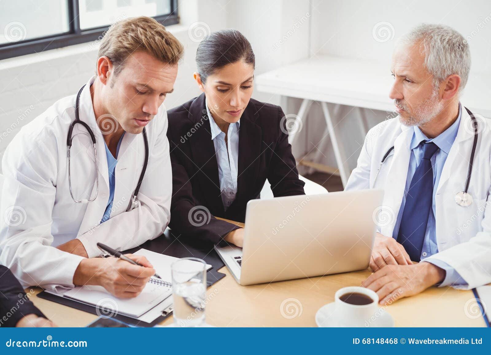 Equipa médica que usa o portátil na sala de conferências