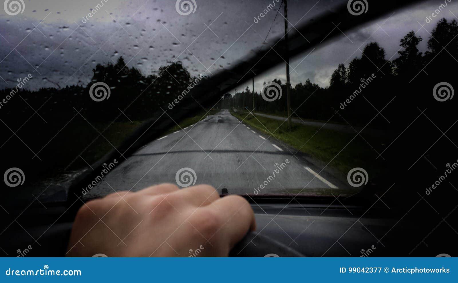 Equipaggi condurre un automobile sulla strada pubblica durante la piovosità pesante con le goccioline di acqua sui tergicristalli