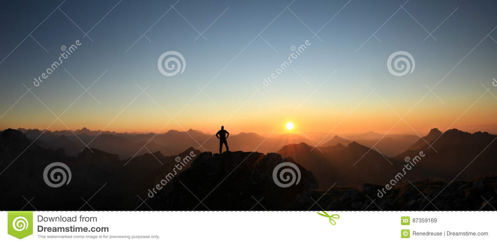 Equipaggi il raggiungimento della sommità che gode della libertà e che guarda verso il tramonto delle montagne