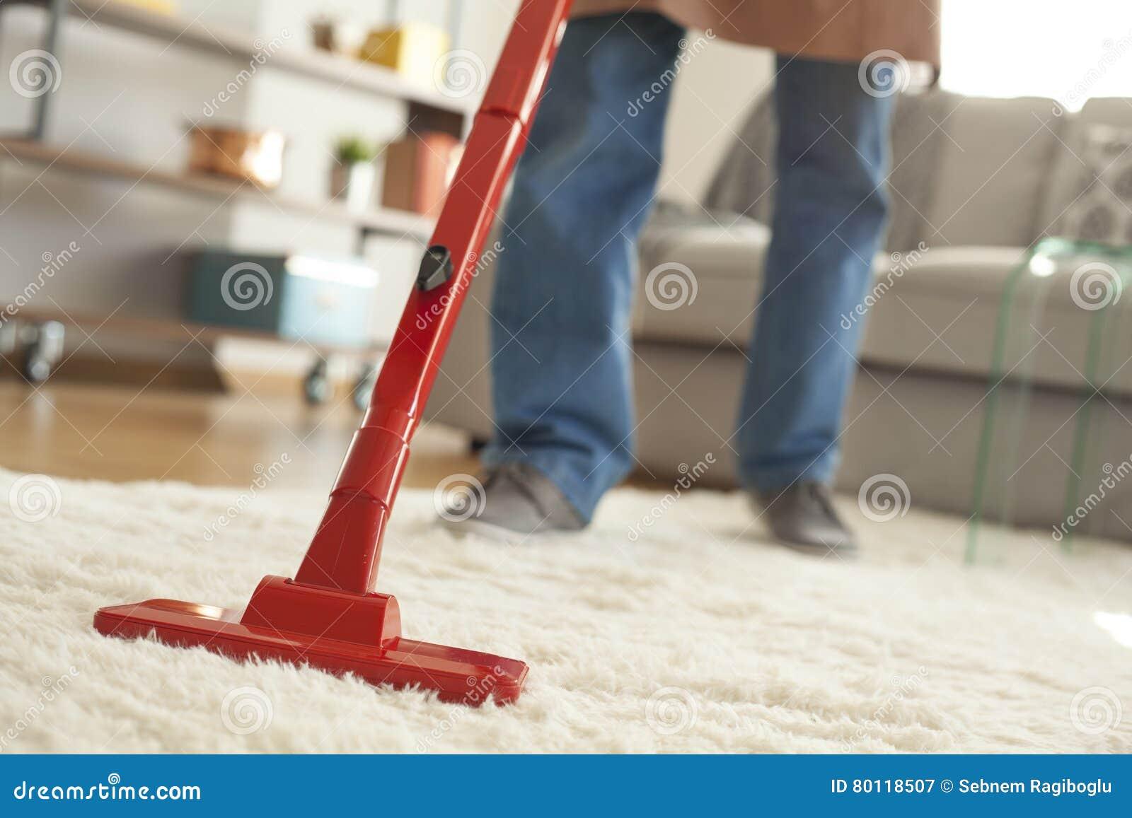 Equipaggi il tappeto di pulizia con un aspirapolvere nella sala