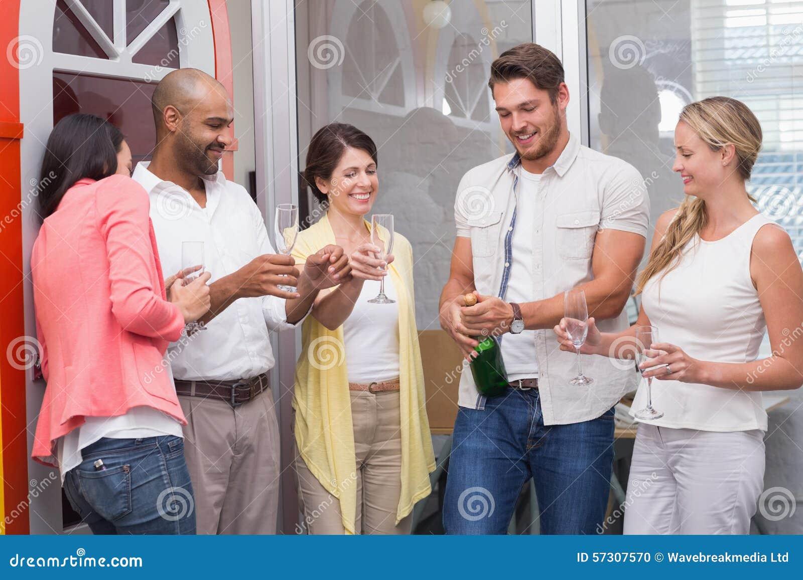 Equipaggi la bottiglia schioccante di champagne con il suo gruppo