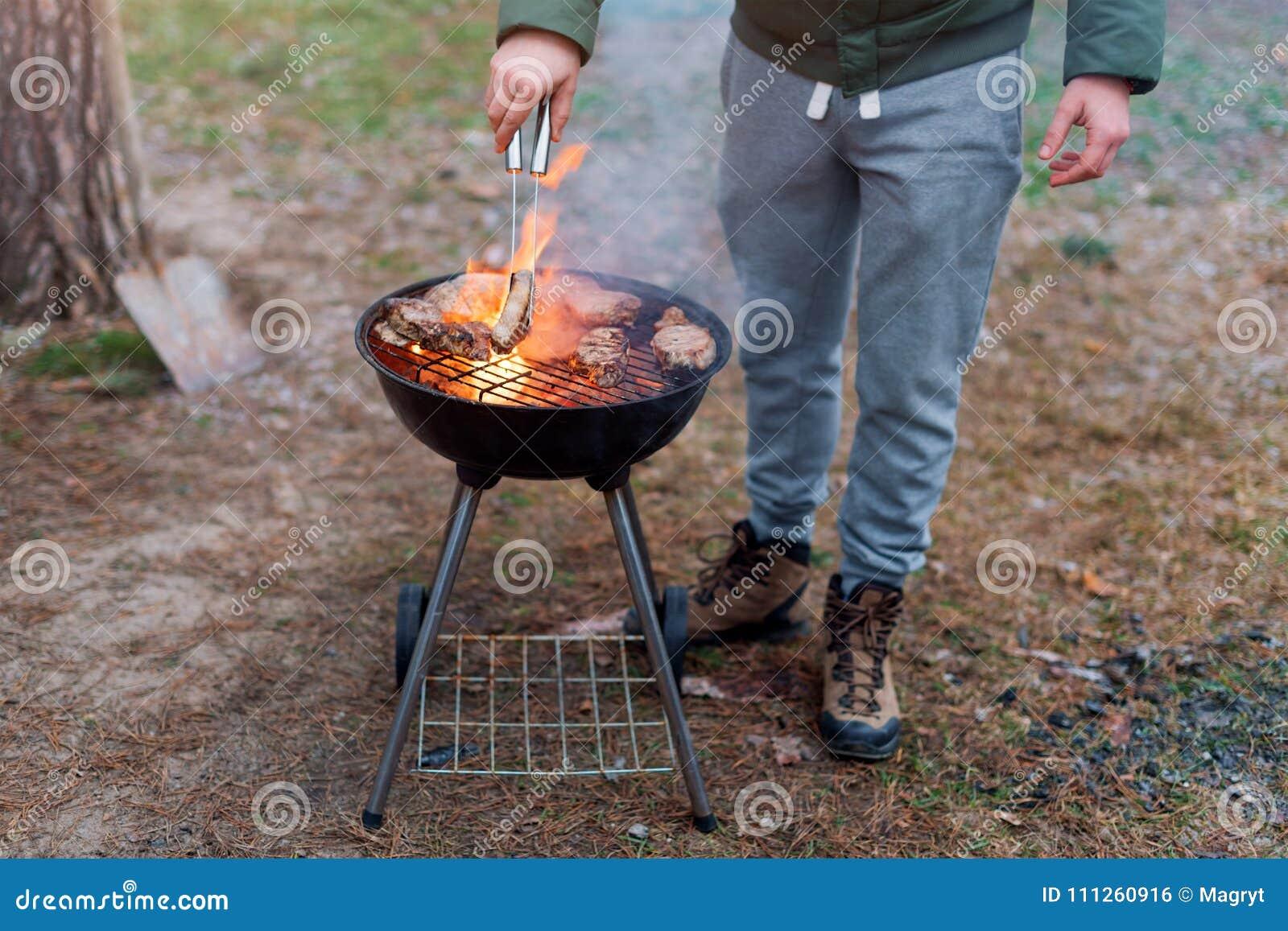 Equipaggi la cottura, solo le mani, lui sta grigliando la carne o la bistecca per un piatto Carne arrostita deliziosa sulla grigl