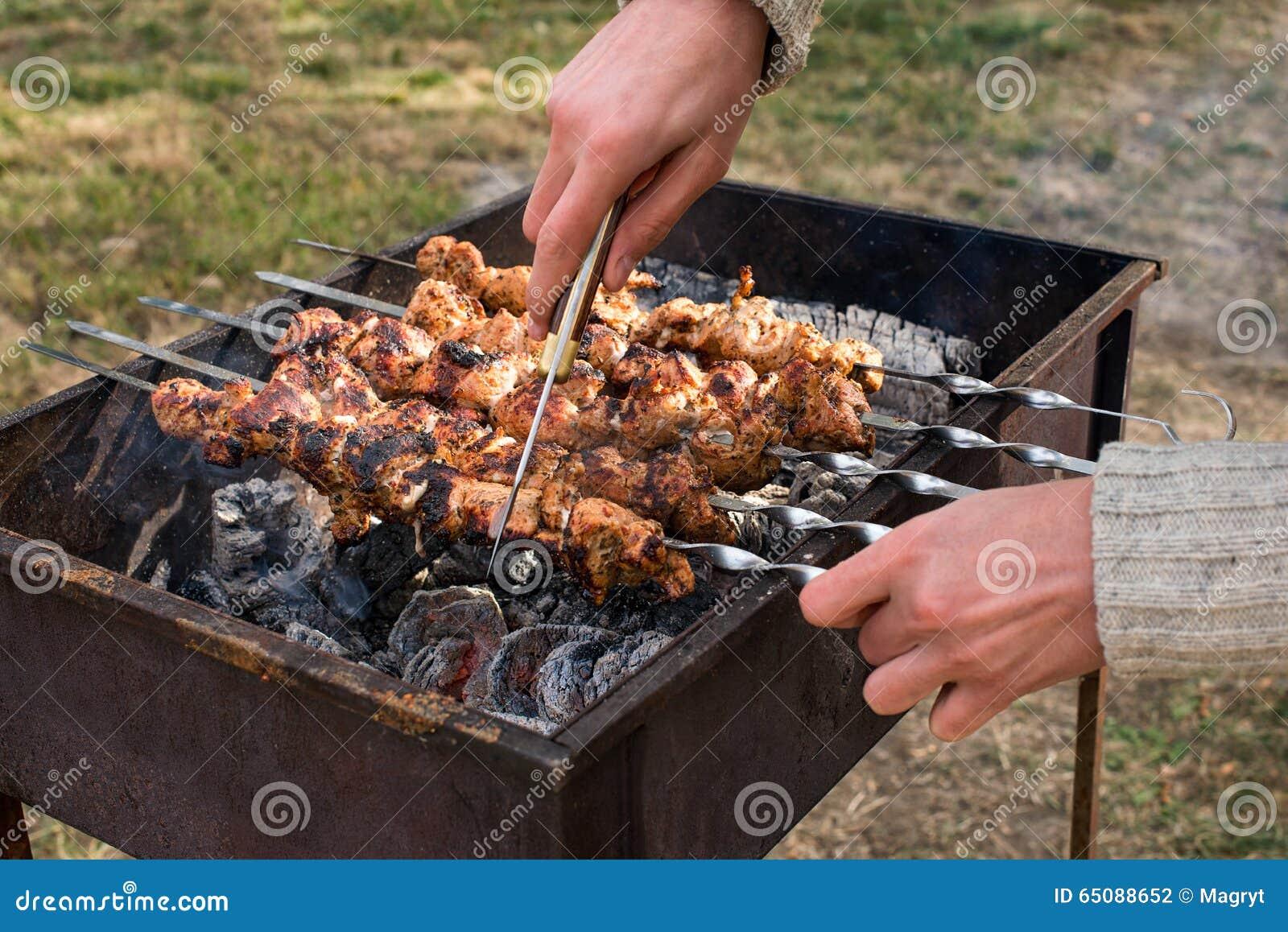Equipaggi la cottura, solo le mani, lui sta tagliando la carne o la bistecca per un piatto Carne arrostita deliziosa sulla grigli