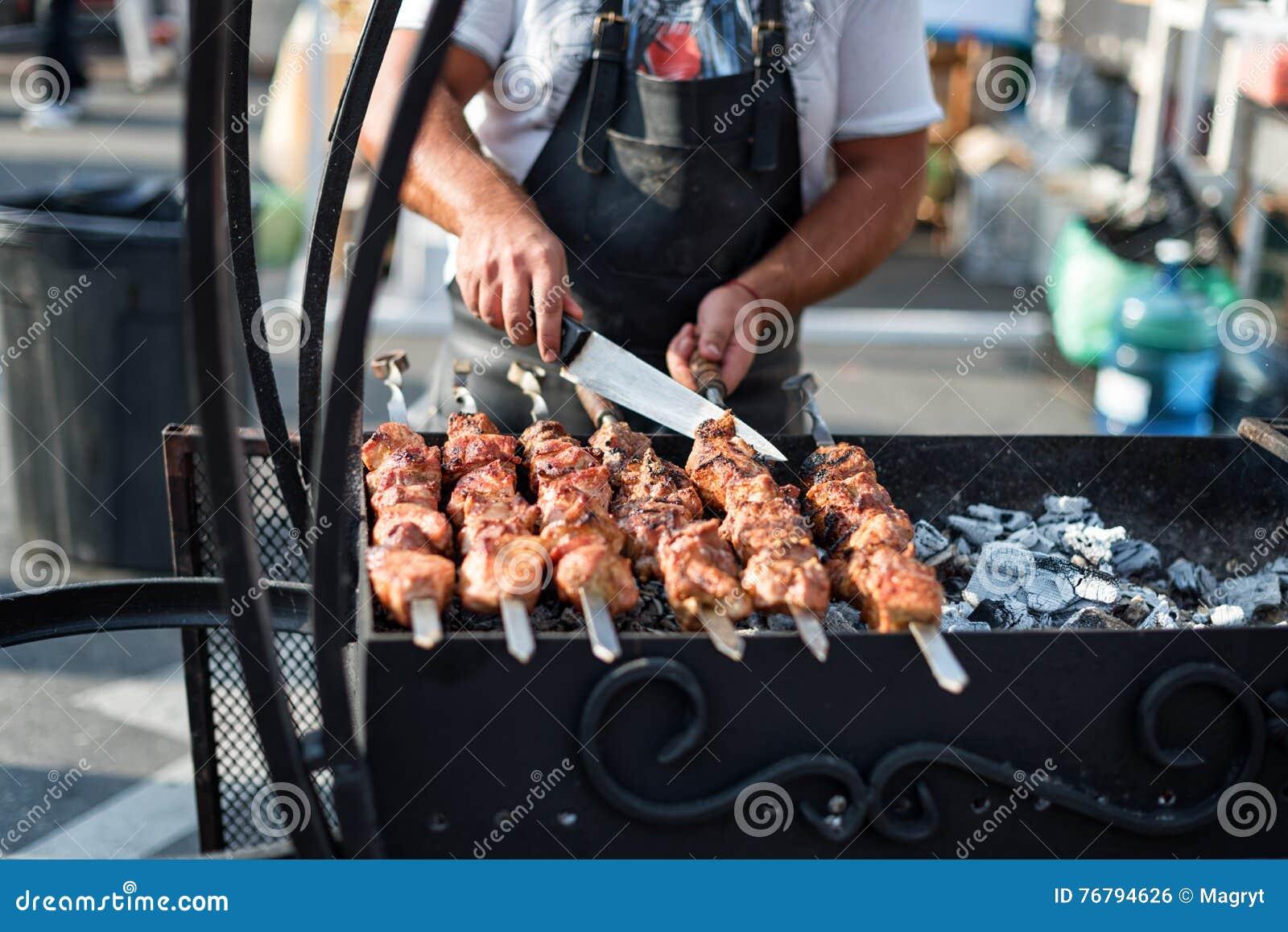 Equipaggi la cottura, solo le mani, lui sta tagliando la carne o la bistecca per un piatto Griglia deliziosa Fine settimana del b