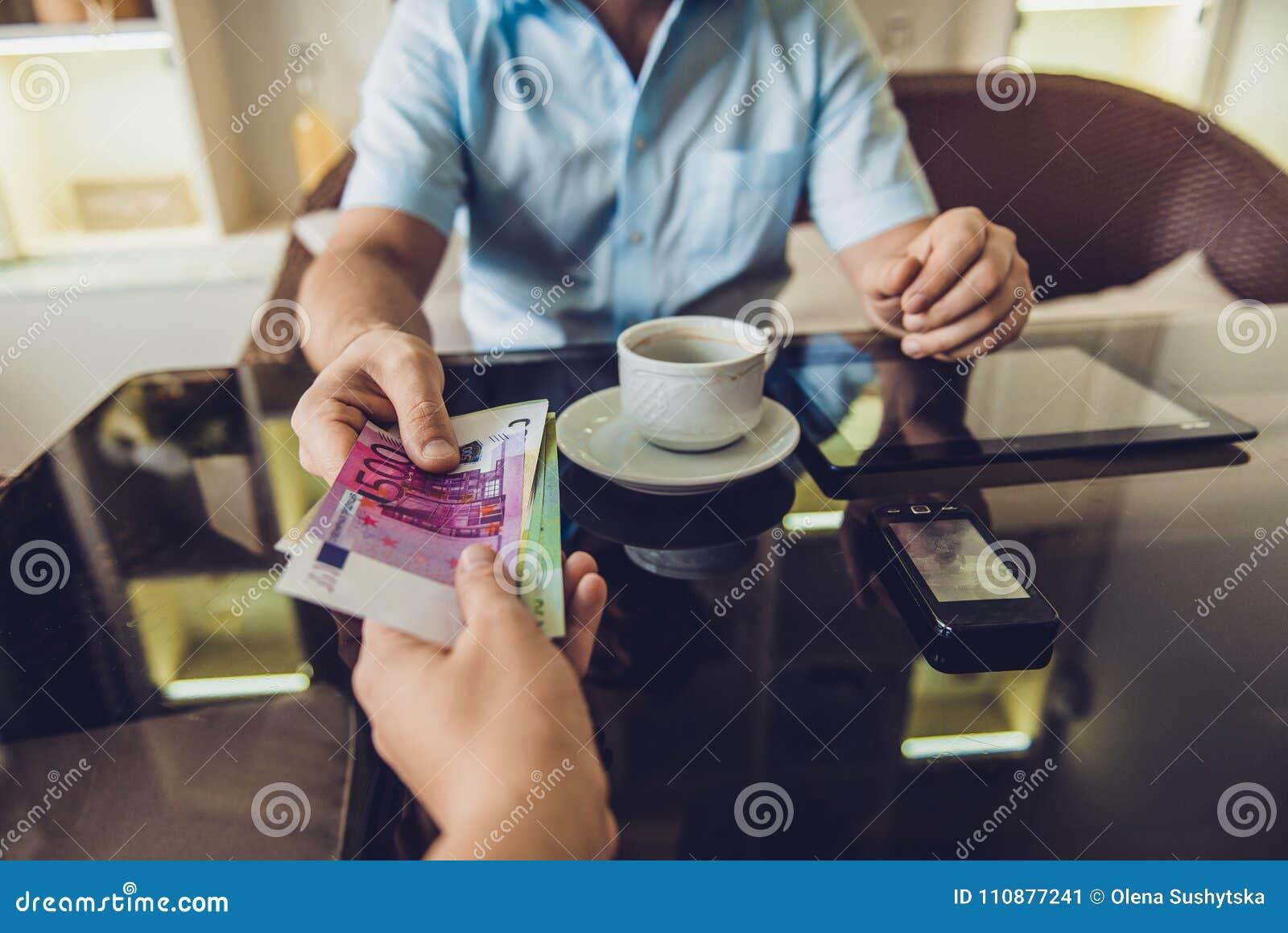 Equipaggi la seduta nei soldi di elasticità del caffè ad un altro uomo