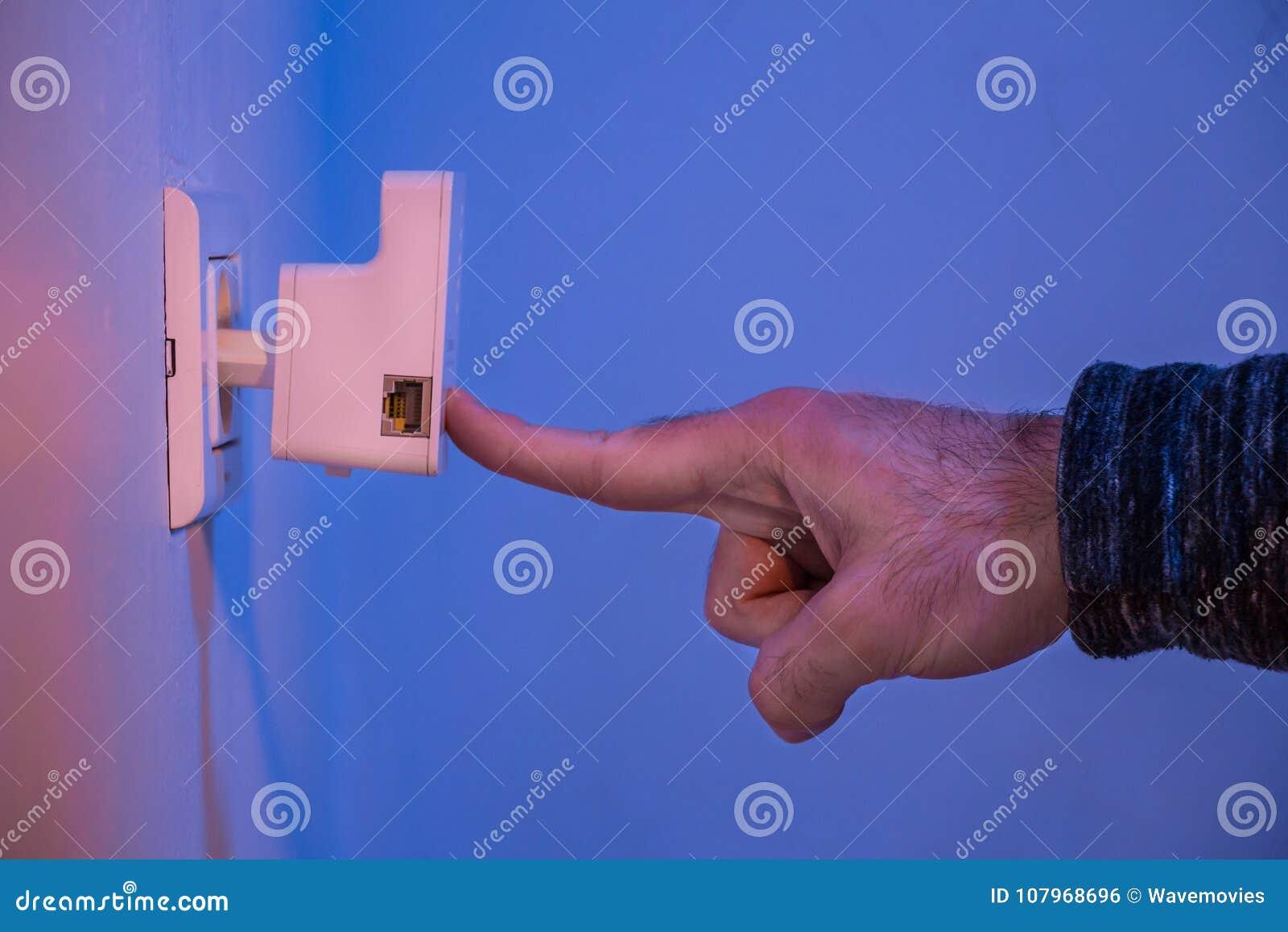 Equipaggi la stampa con il suo dito sul bottone di WPS sul ripetitore di WiFi che i
