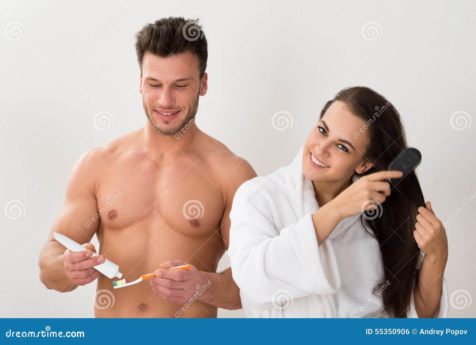 Equipaggi lo spazzolino da denti della tenuta e la sua moglie che pettinano i suoi capelli