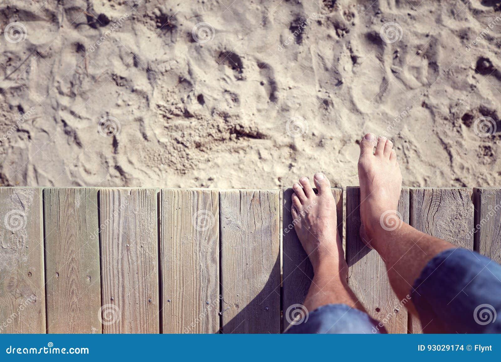 Equipaggi a piedi nudi fare un passo fuori dal sentiero costiero sulla sabbia della spiaggia