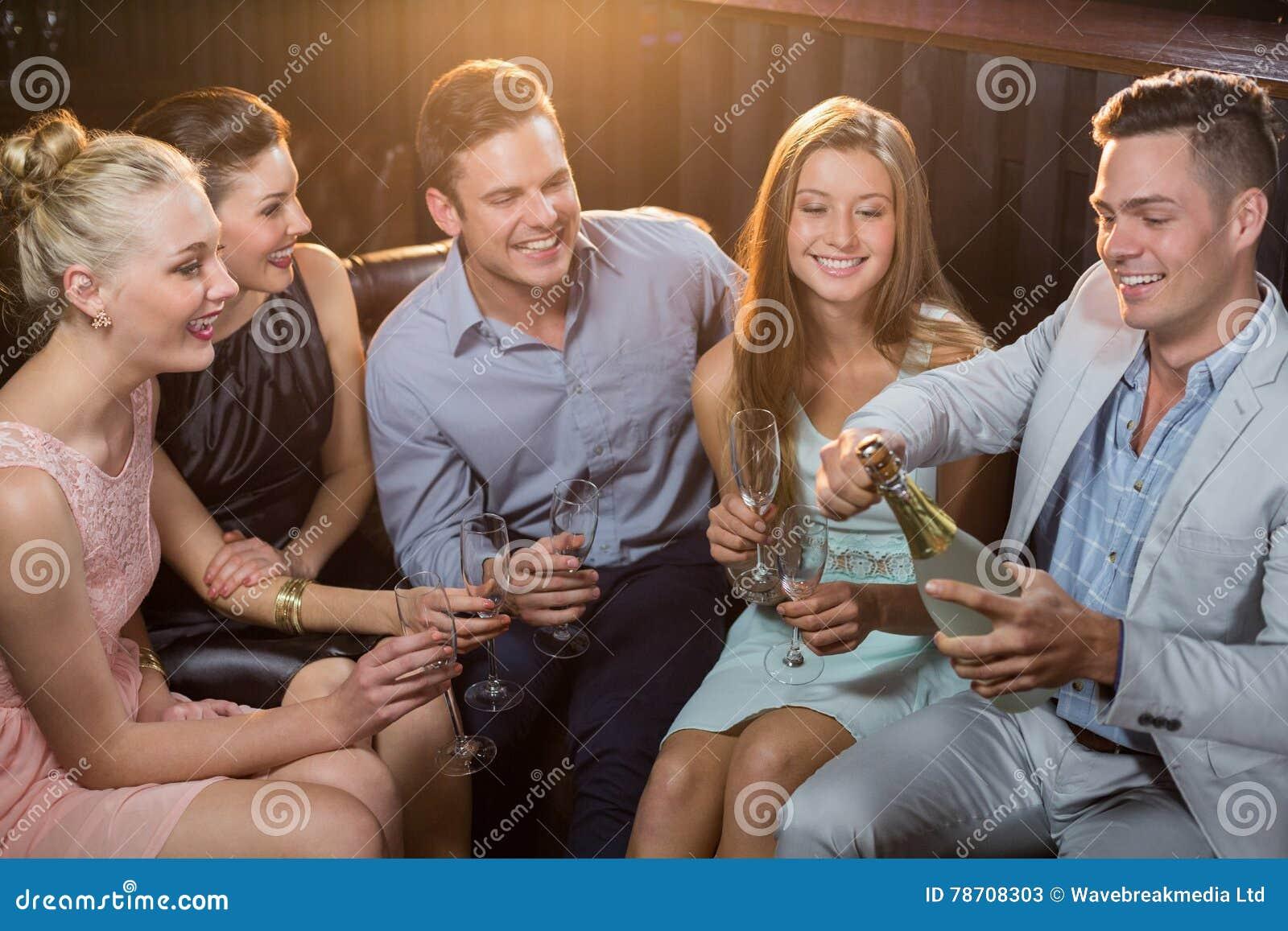 Equipaggi schioccare una bottiglia del champagne mentre amici che lo guardano