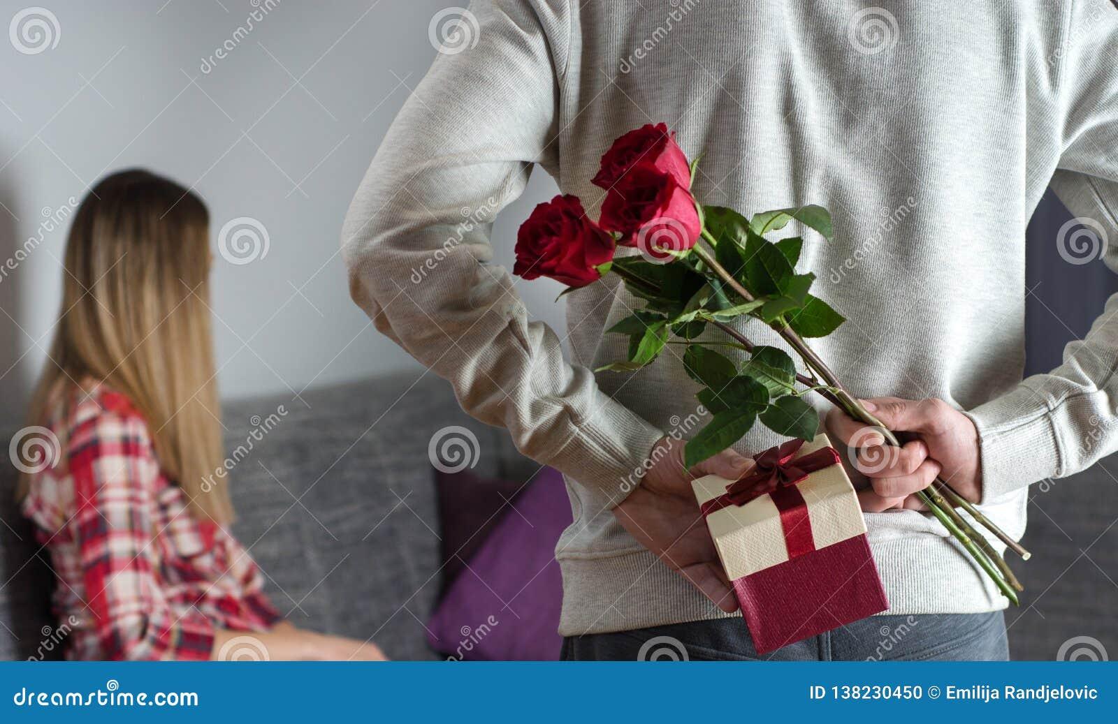 Equipaggia le mani che si nascondono tenendo il mazzo elegante delle rose rosse ed il regalo con il nastro bianco dietro la parte