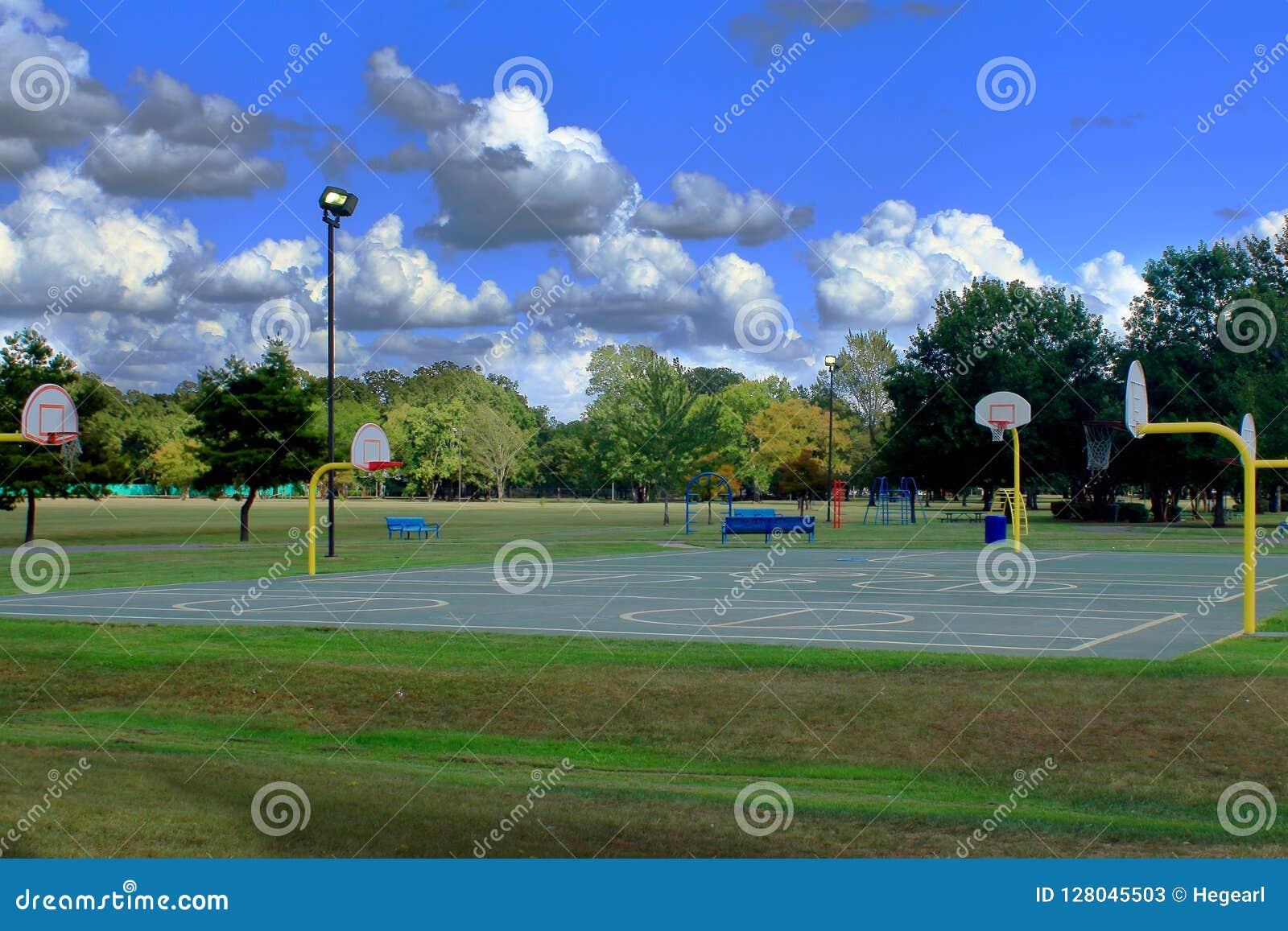Equipamento colorido do campo de jogos em um parque público com os céus azuis profundos