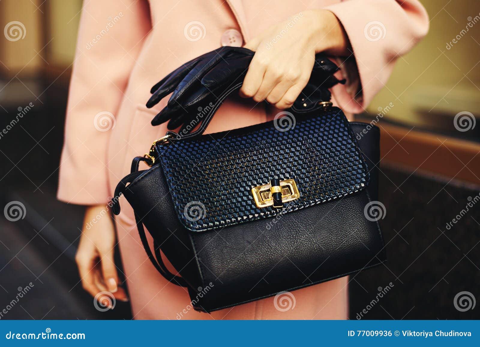 Equipamento elegante Close up da mulher à moda disponivel da bolsa preta do saco de couro Menina elegante na rua fêmea