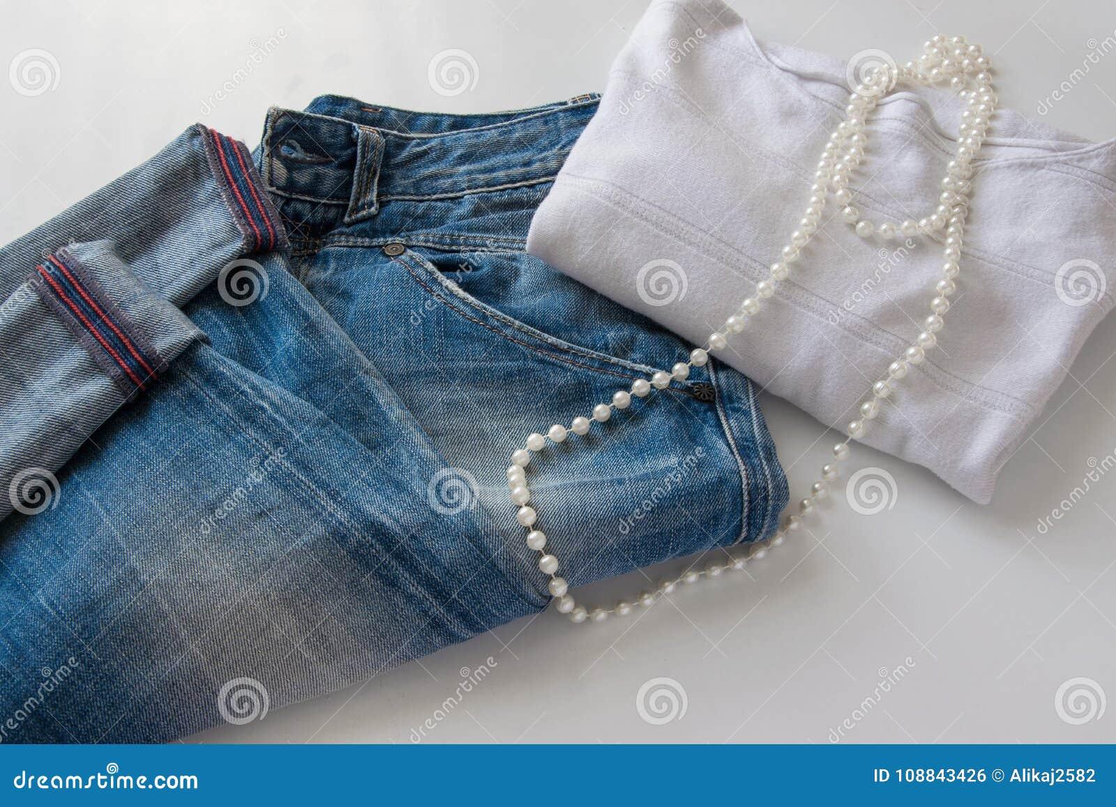 Equipamento ocasional elegante do ` s das mulheres - calças de ganga, camiseta branca e colar branca da pérola