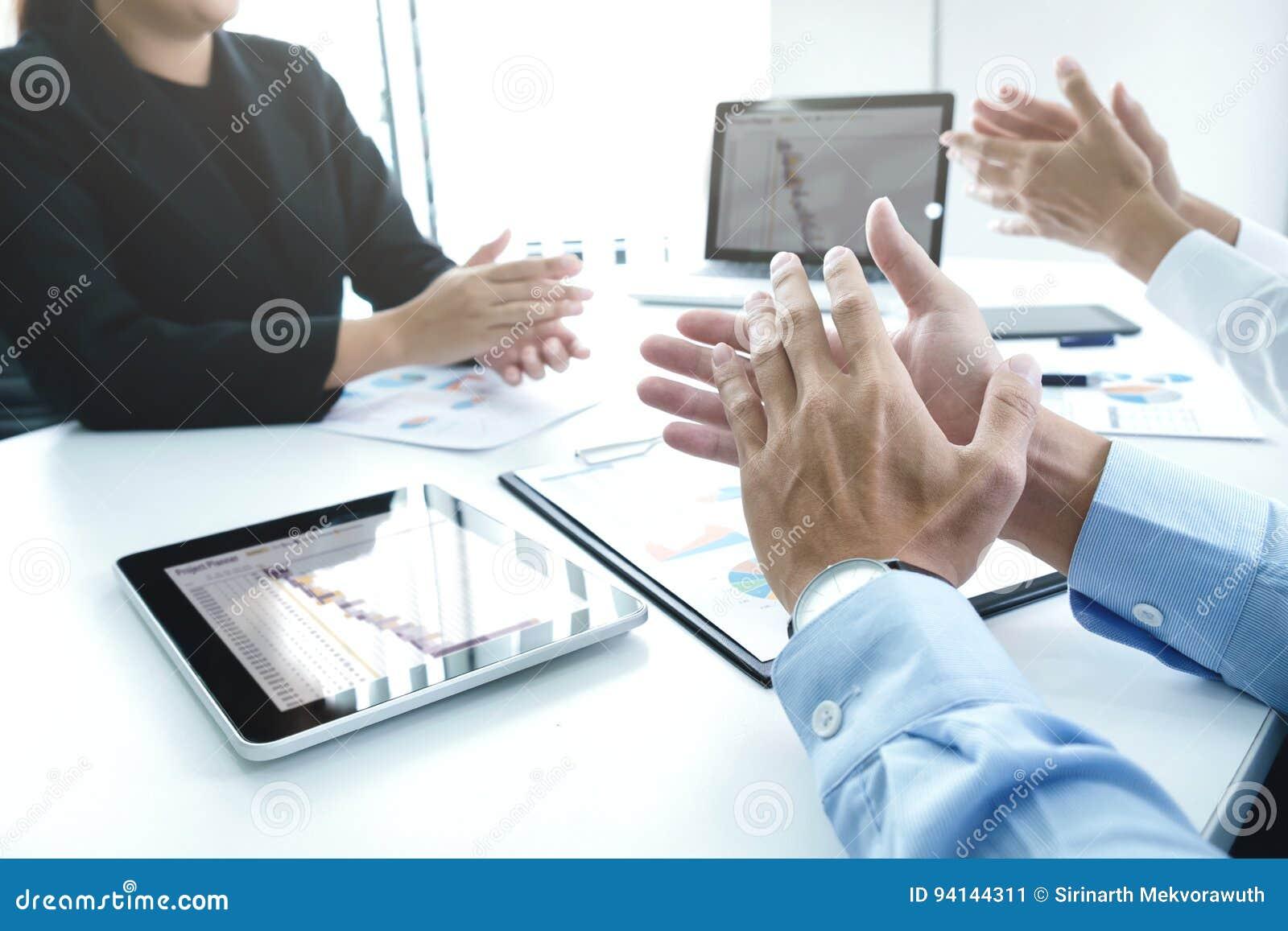 Equipe bem sucedida do negócio que aplaude após o bom negócio