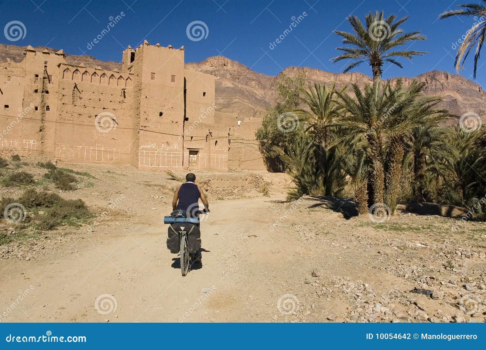 Equipe a ciclagem perto de uma vila pequena em Marrocos sul