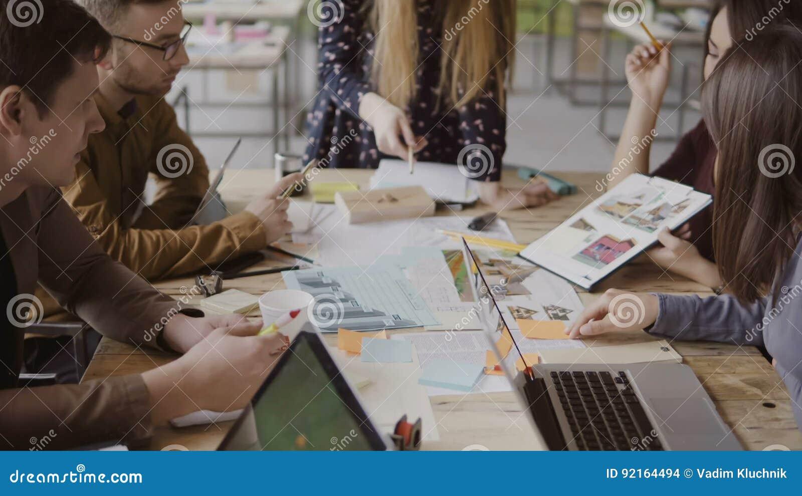 Equipe criativa nova do negócio no escritório moderno Grupo de pessoas multi-étnico que trabalha na concepção arquitetónica junto