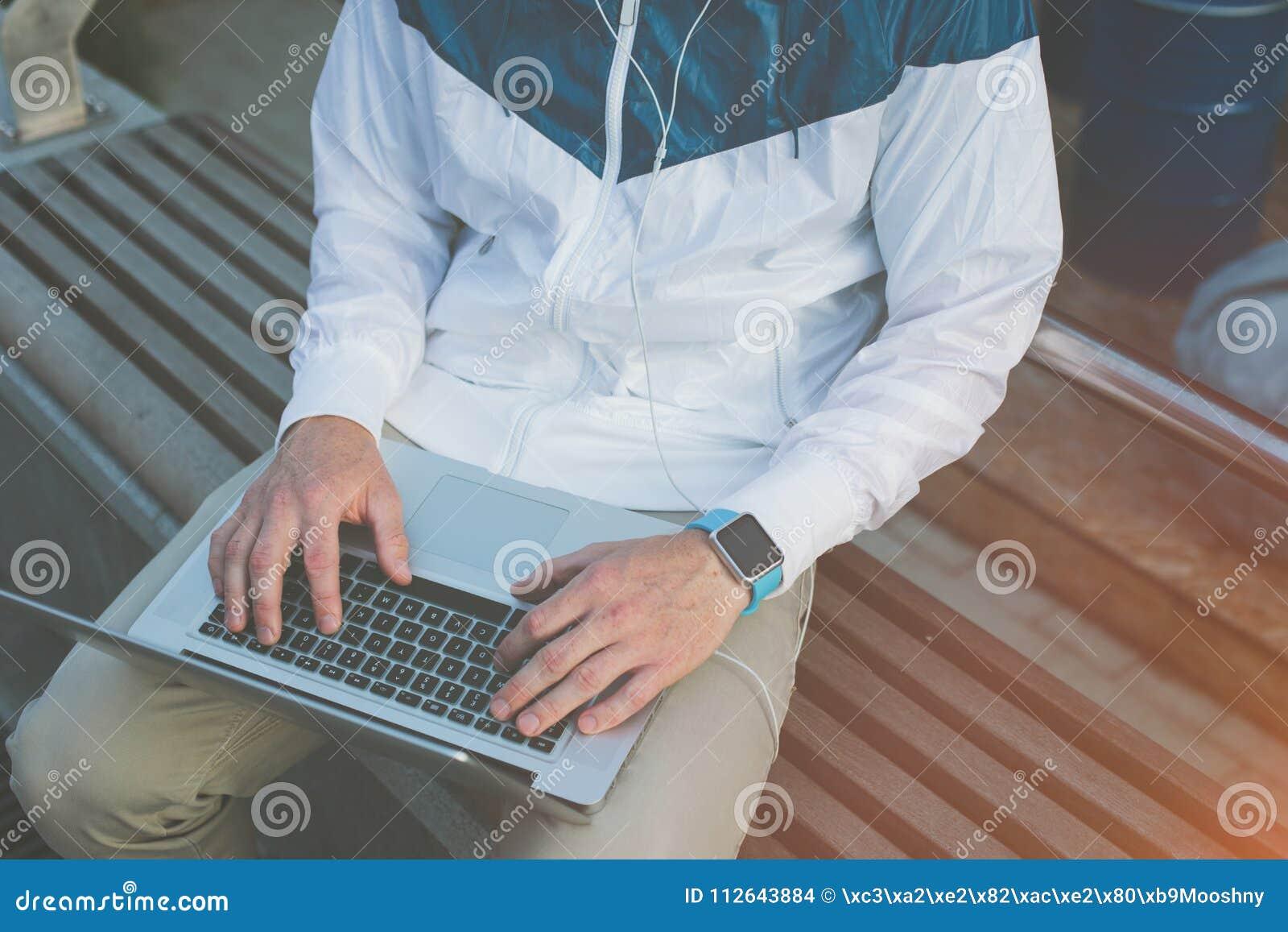 Equipe a datilografia no portátil e o assento no banco fora