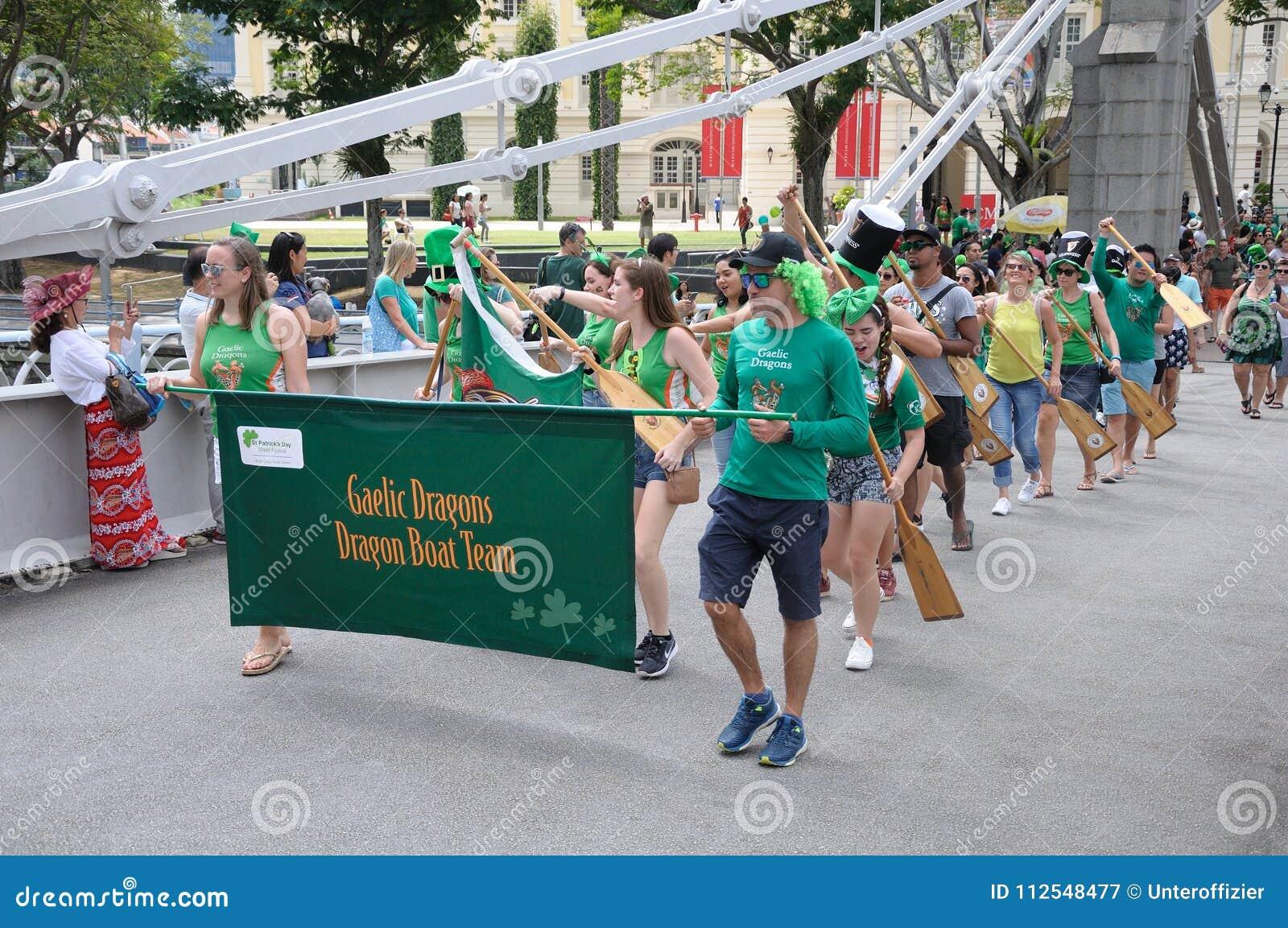 Equipe de Gaelic Dragon do dia do ` s de St Patrick que cruza a ponte de Cavengah em Singapura