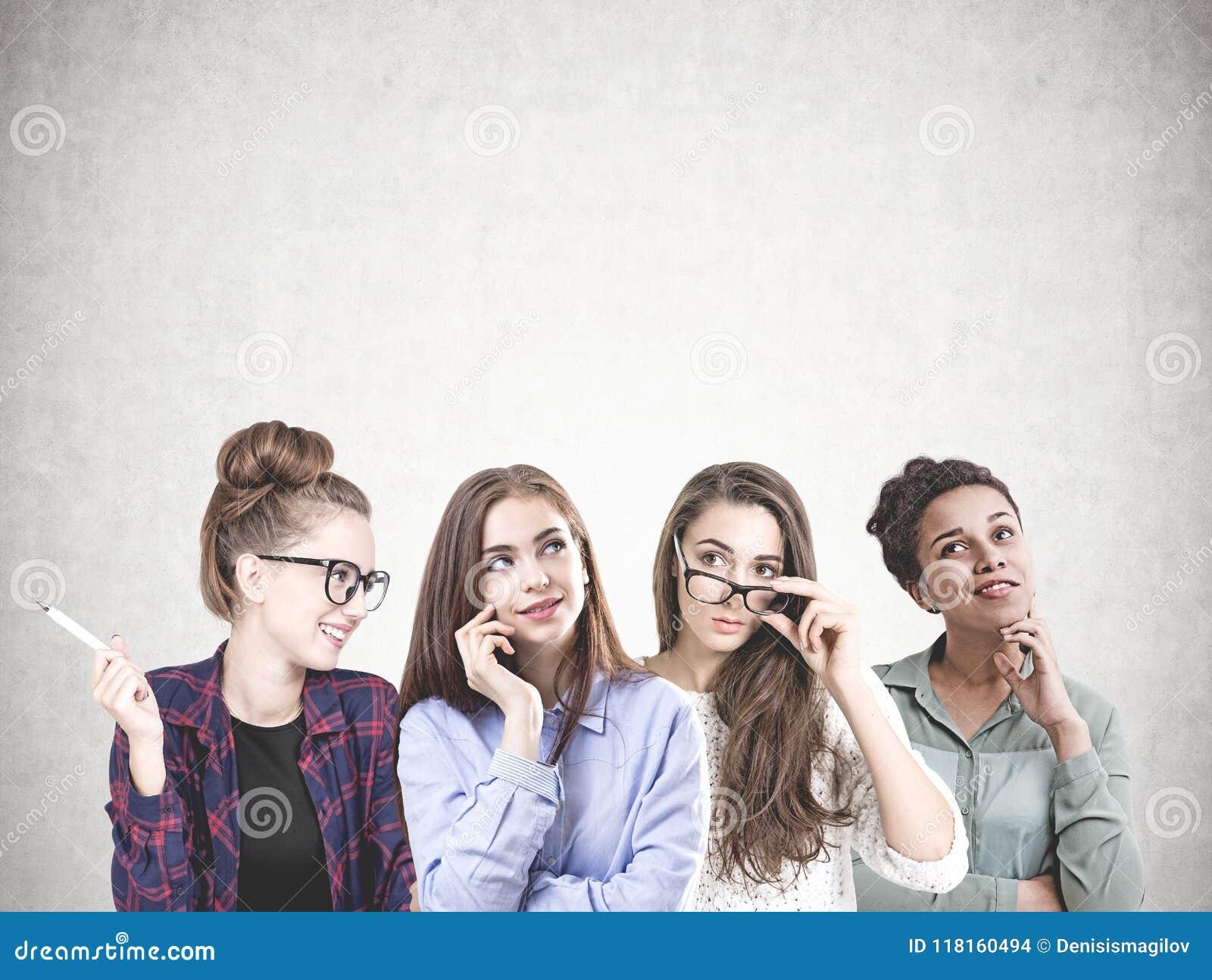 A equipe de jovens mulheres diversa, zomba acima do muro de cimento