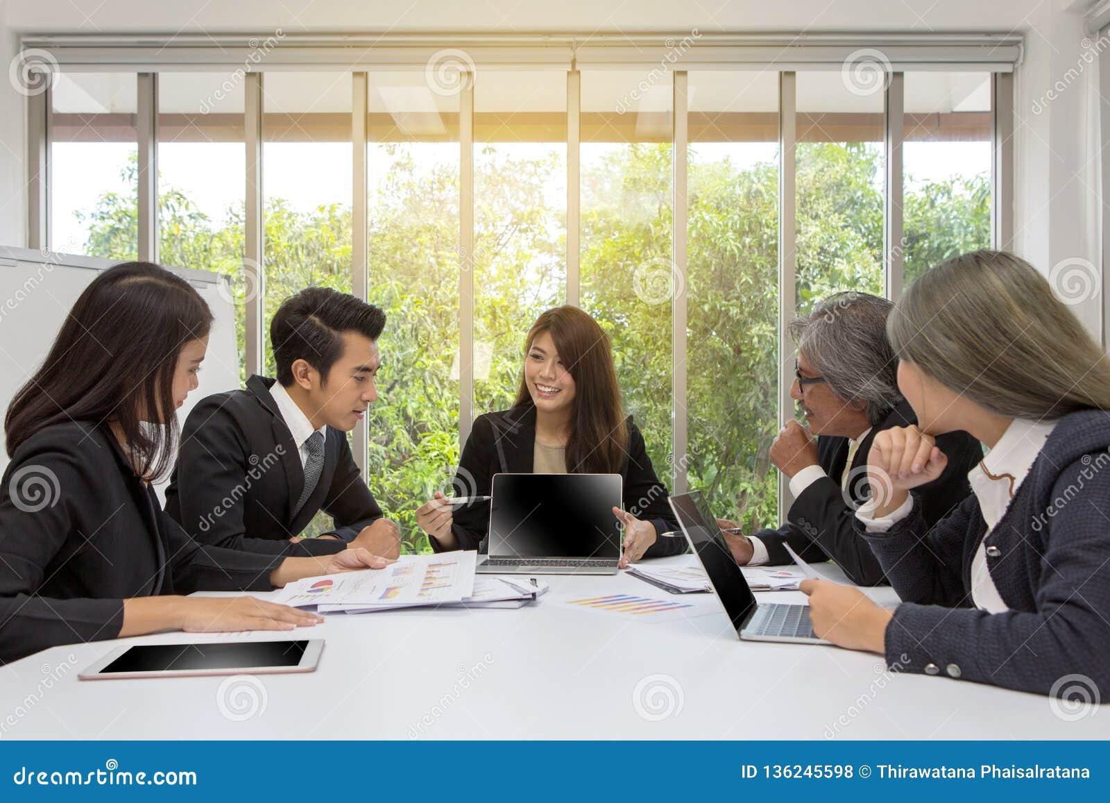 Equipe do negócio asiático que levanta na sala de reunião Sessão de reflexão de trabalho na tabela em uma sala Povos asiáticos Ho