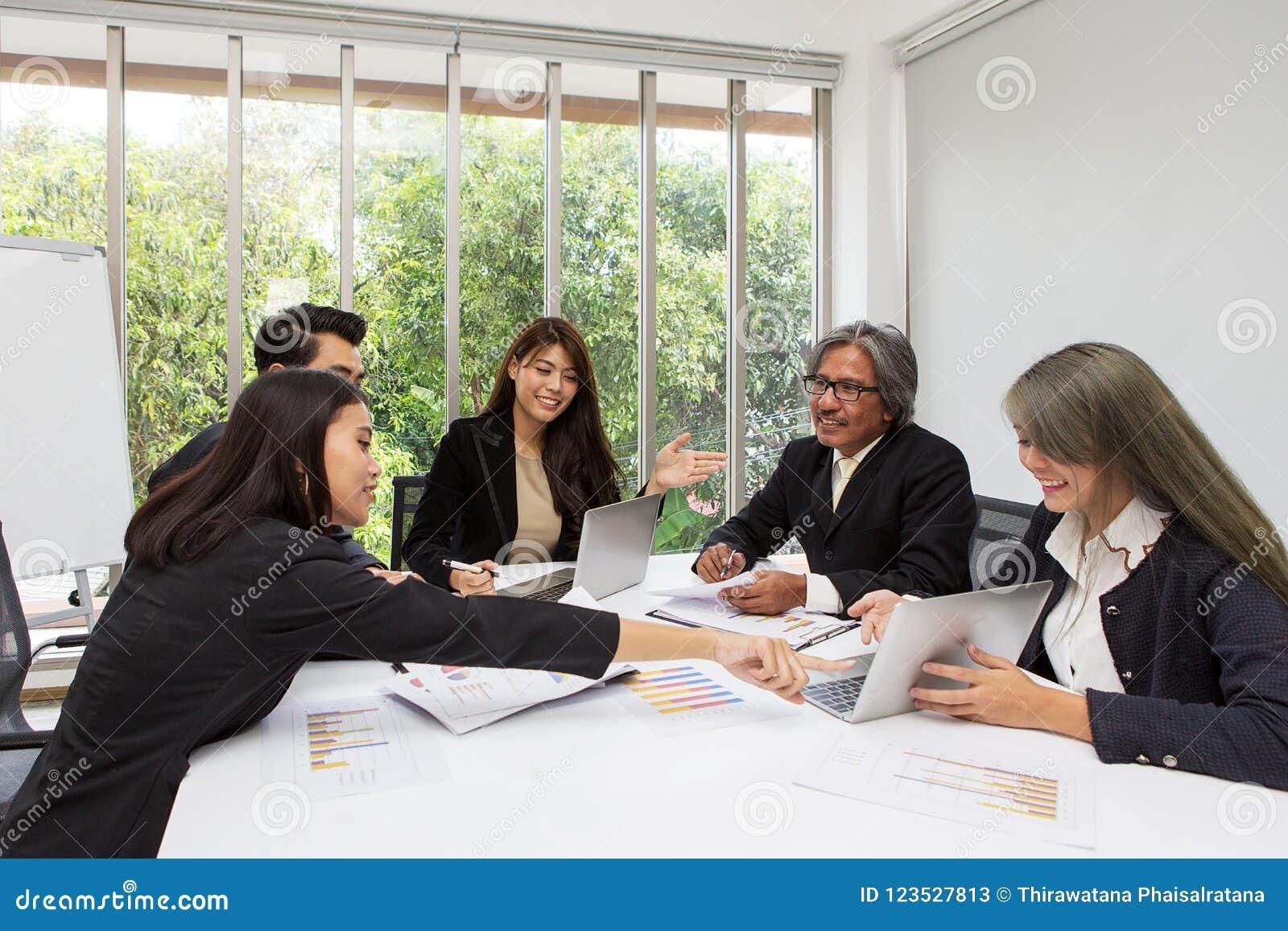 Equipe do negócio asiático que levanta na sala de reunião Sutiã de trabalho do grupo