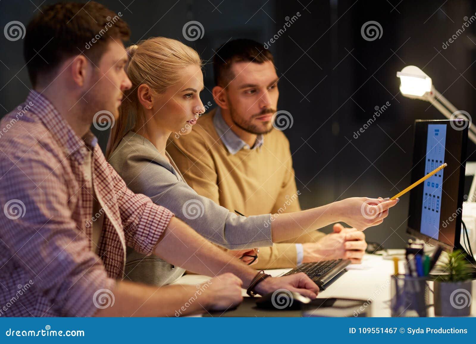 Equipe do negócio com o computador que trabalha tarde no escritório