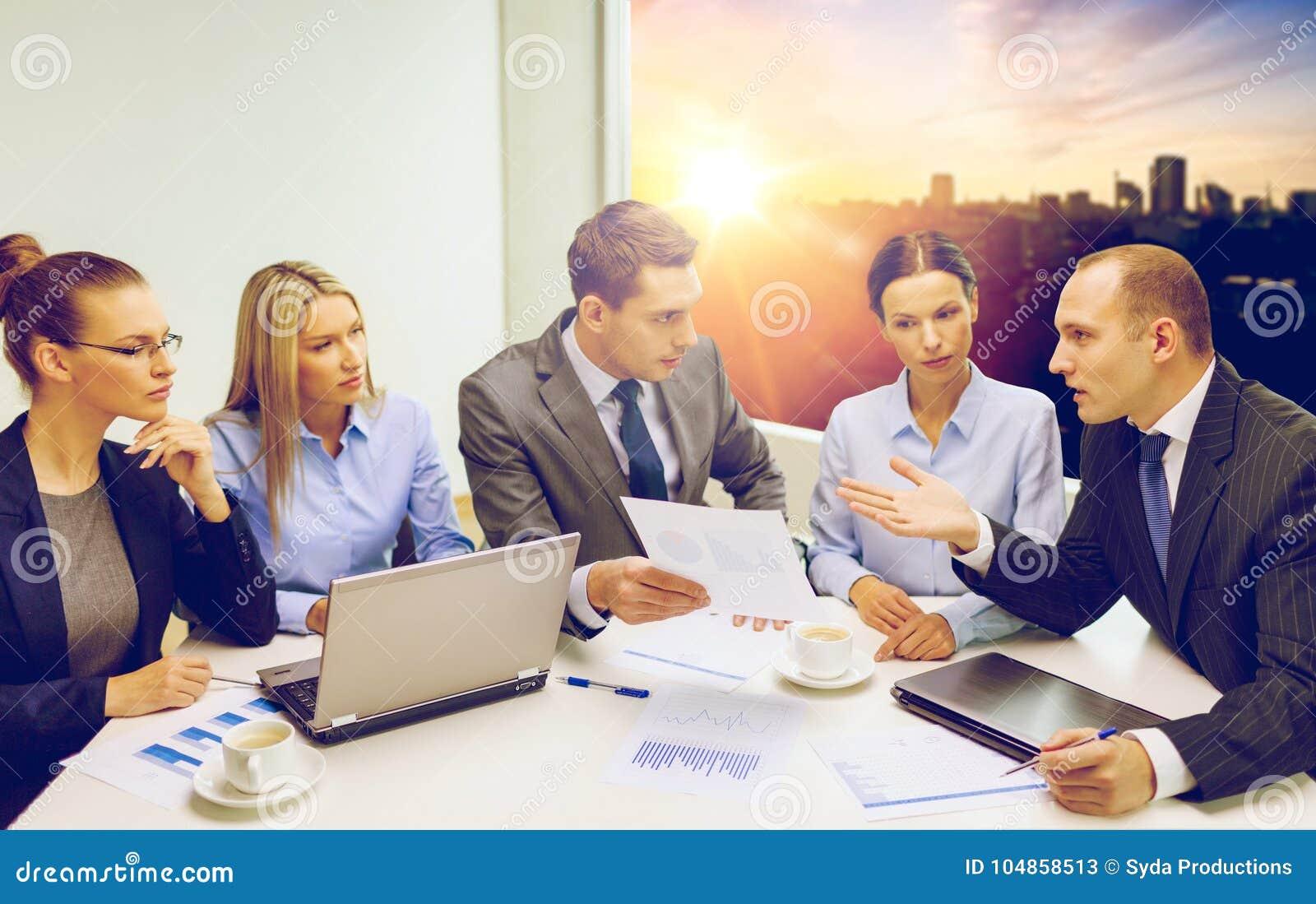Equipe do negócio com o portátil que tem a discussão