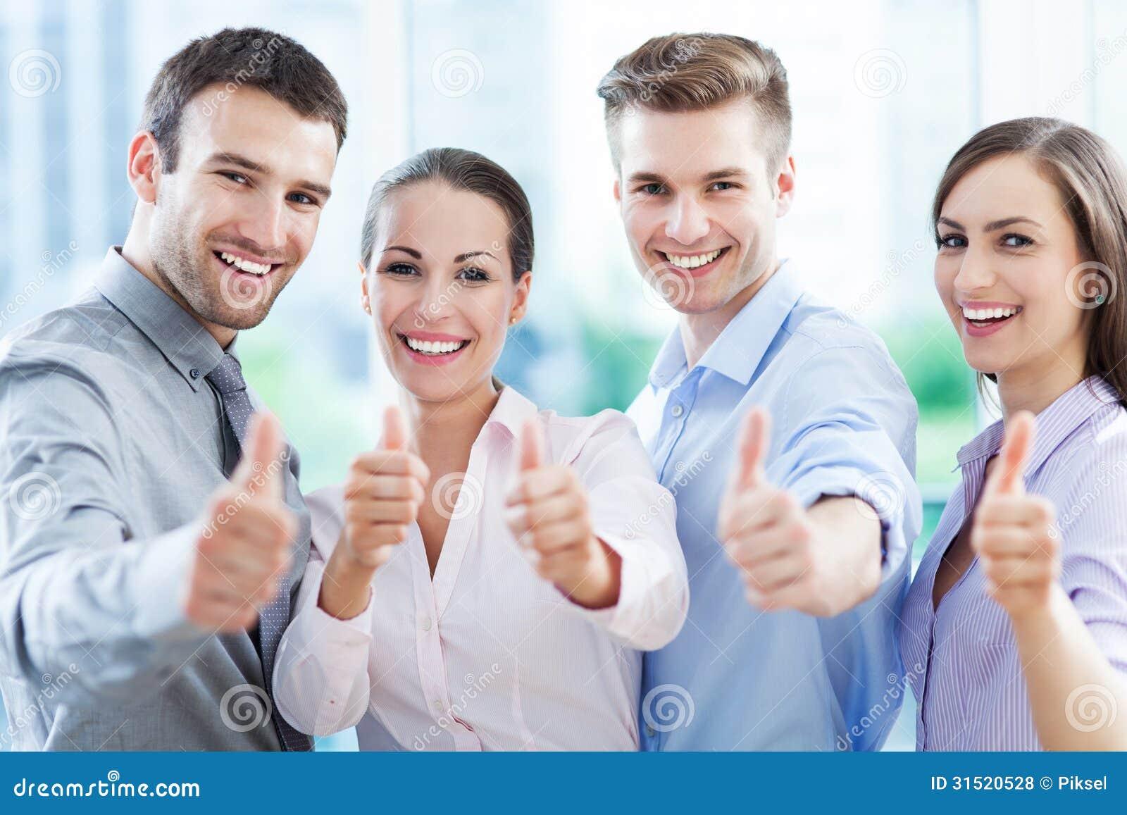 Equipe do negócio com polegares acima