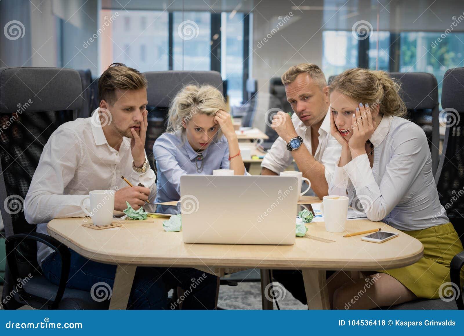 Equipe do negócio que olha o computador com expressões chocadas