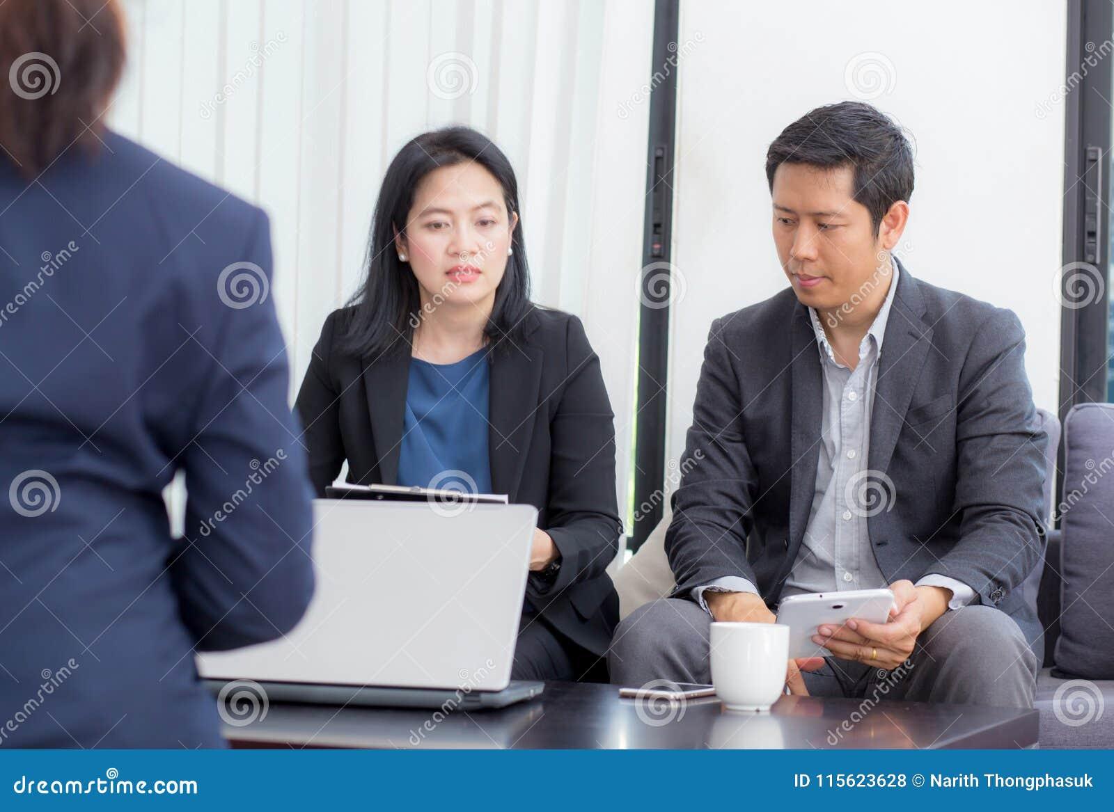 Equipe dos povos do negócio três que trabalham junto em um portátil com durante uma reunião que senta-se em torno de uma tabela