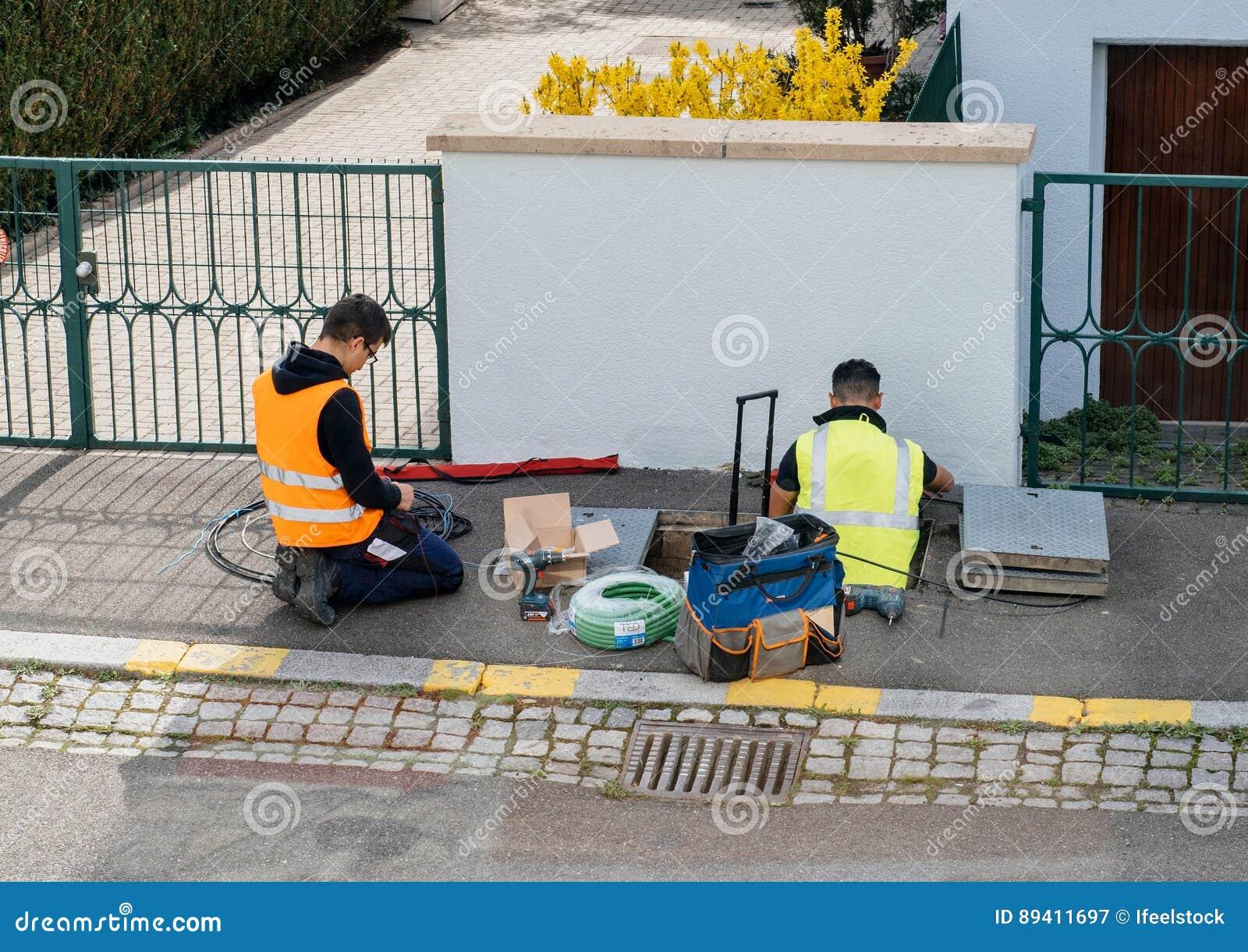 Equipe dos trabalhadores que trabalham na aplicação dos cabos de fibra ótica