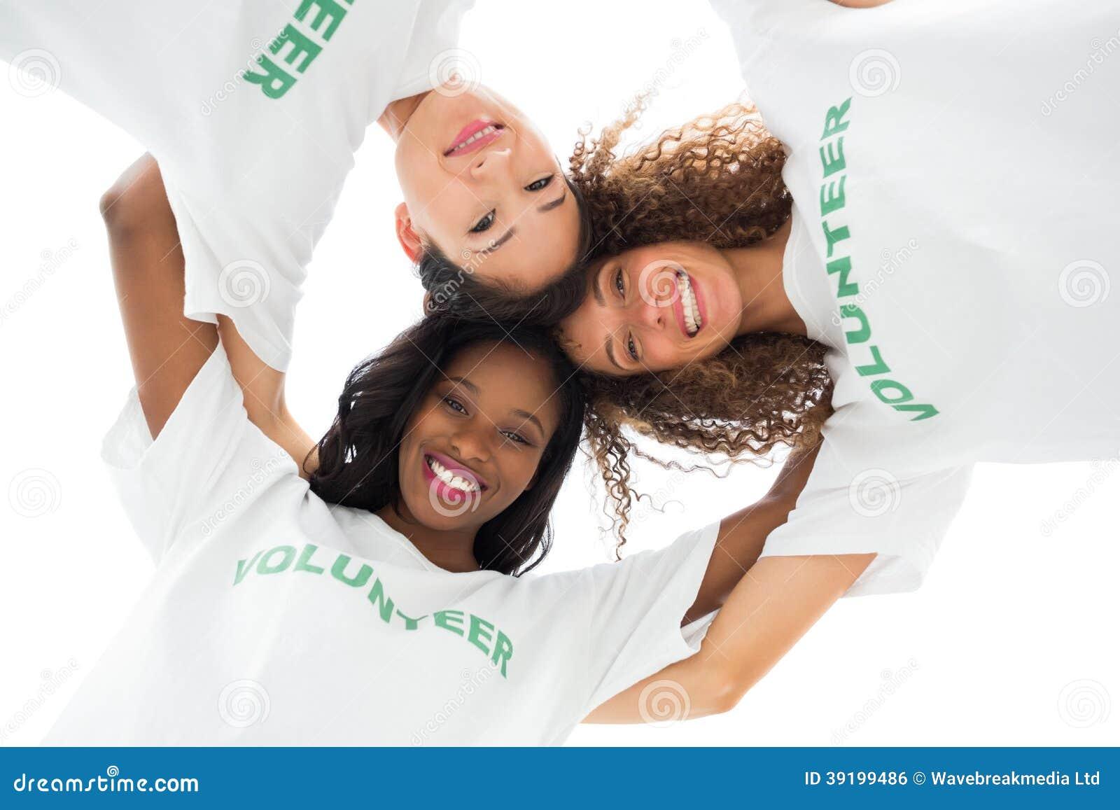 Equipe dos voluntários felizes que abraçam e que olham para baixo na câmera