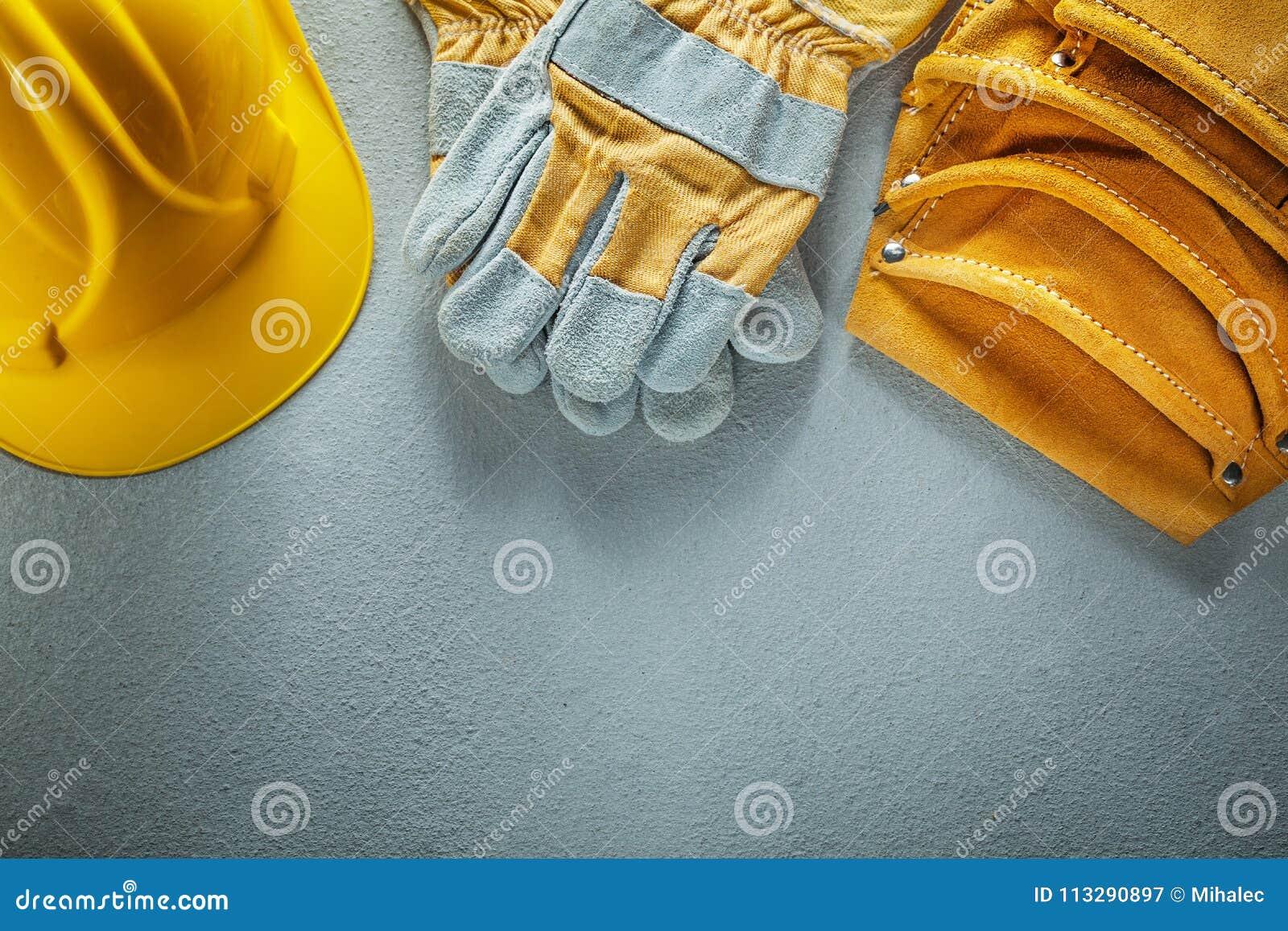 Equipe el casco de los guantes de la seguridad de la correa en fondo concreto