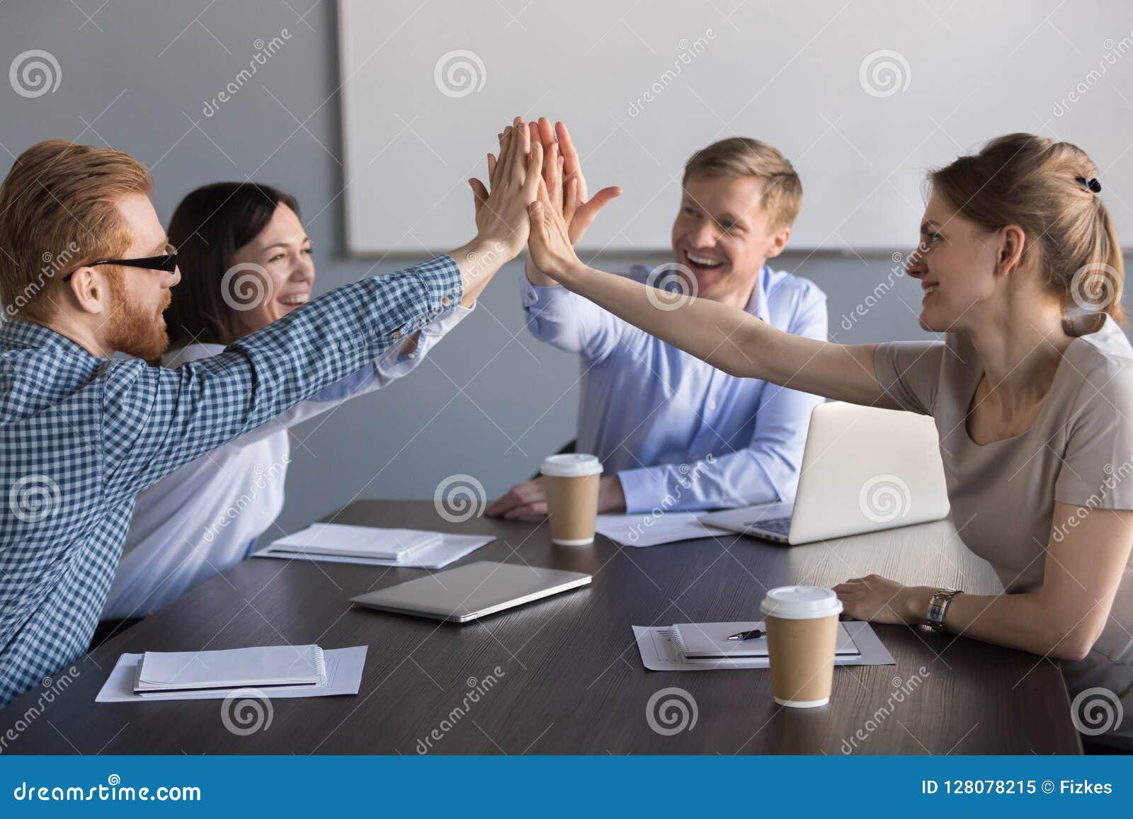 Equipe entusiasmado do negócio dos empregados que dão a elevação cinco durante o meeti