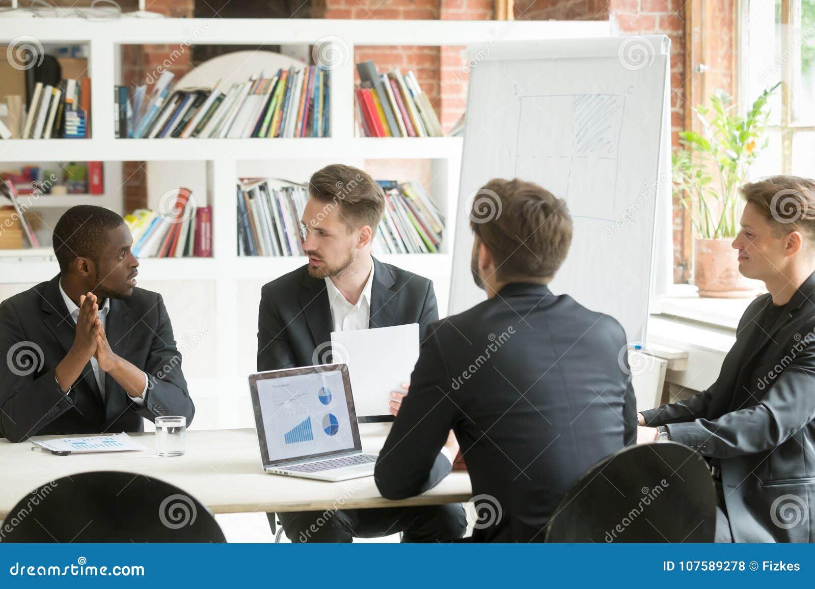 A equipe executiva diversa do negócio que discute o trabalho resulta no corpo