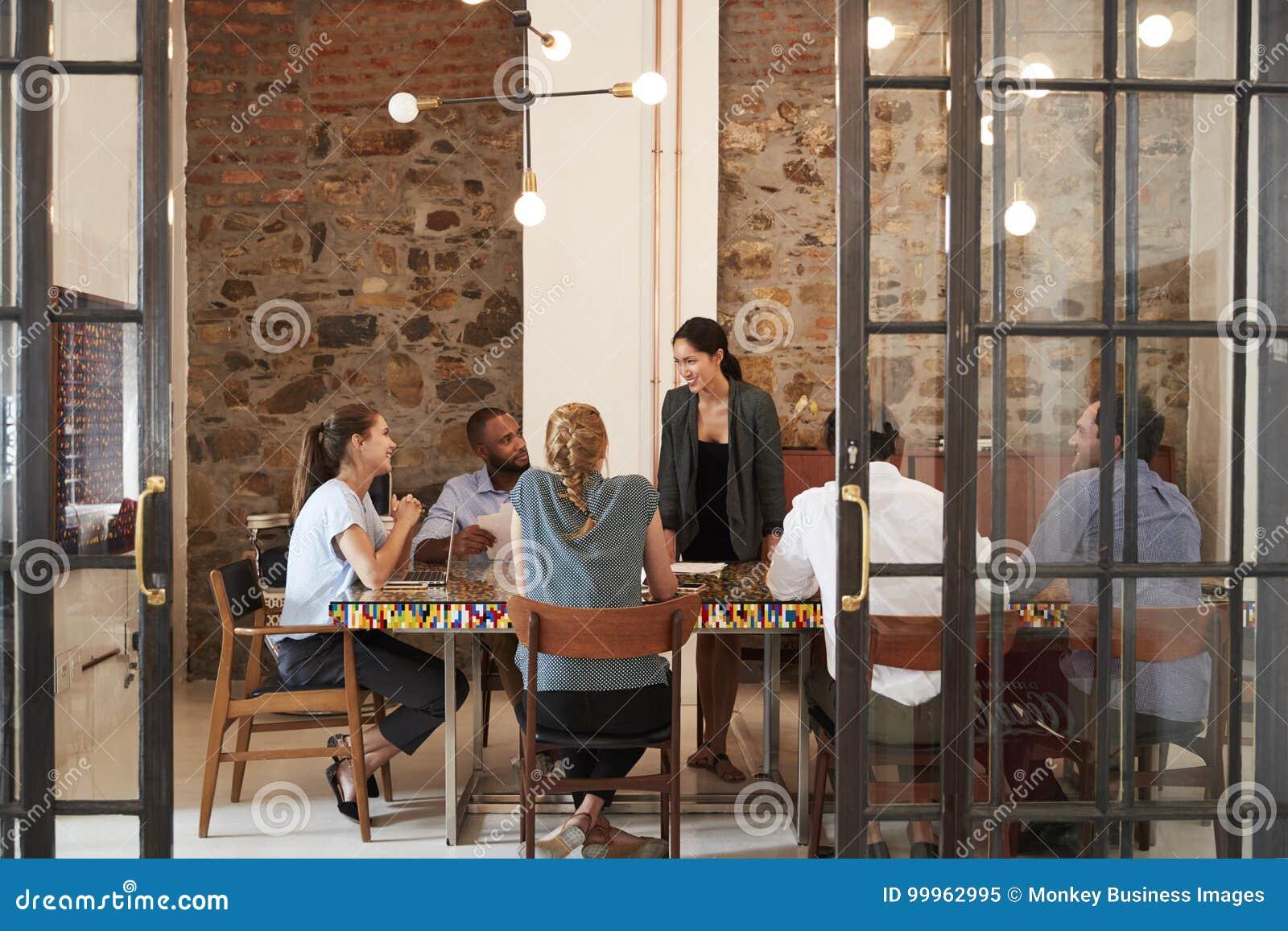 Equipe fêmea do negócio do endereçamento do chefe em uma sala de reunião