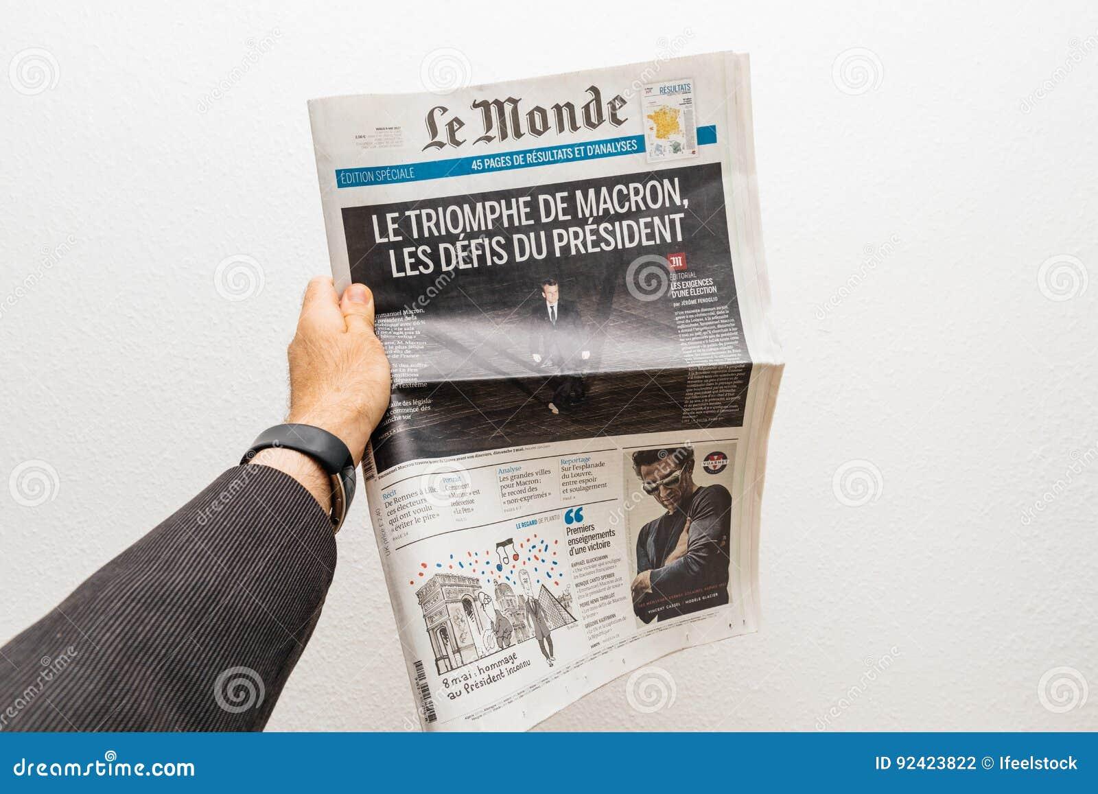 Equipe guardar o jornal de Le Monde com Emmanuel Macron no primeiro pag
