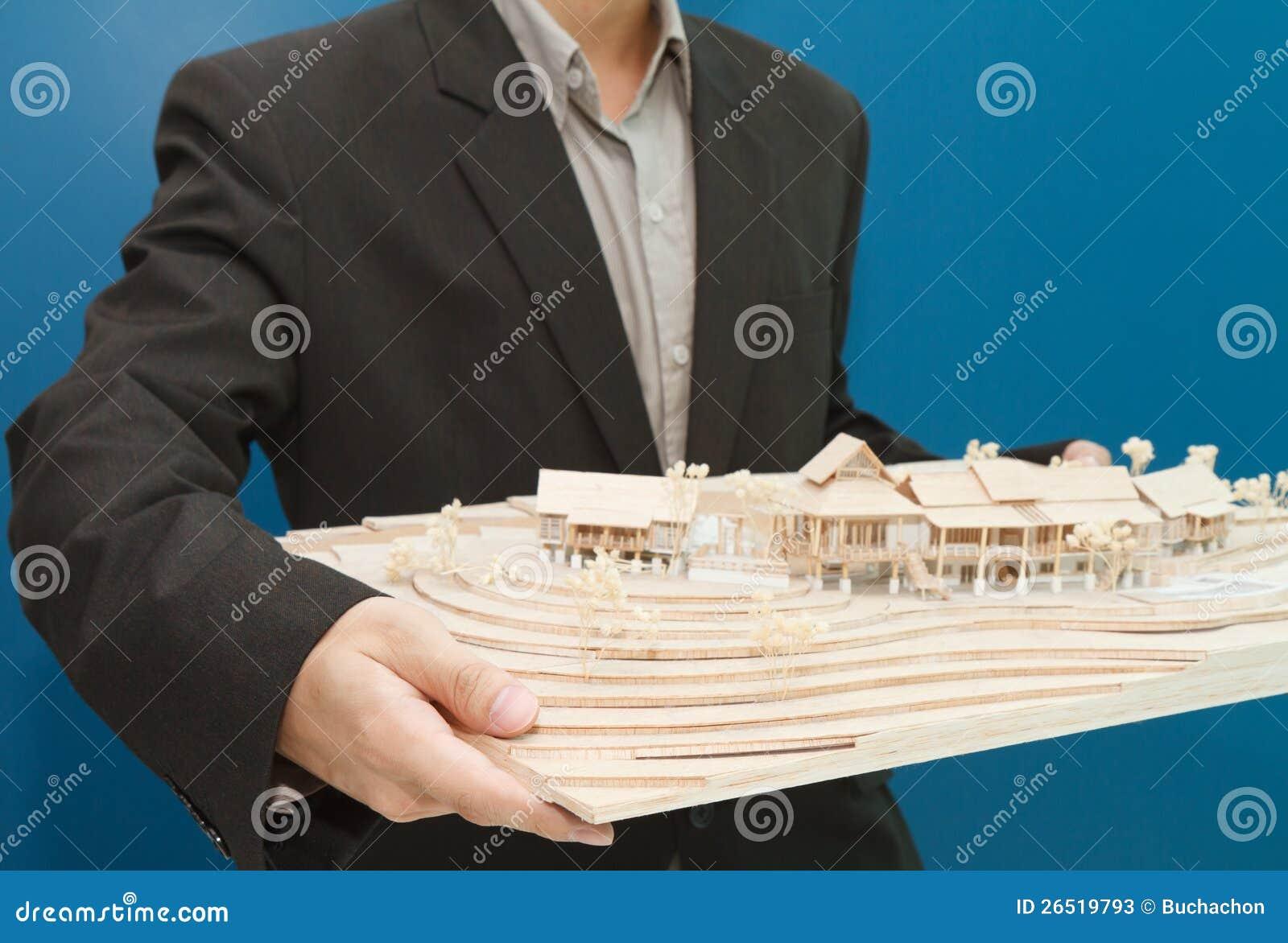 Equipe guardarar um modelo de uma casa em suas mãos.