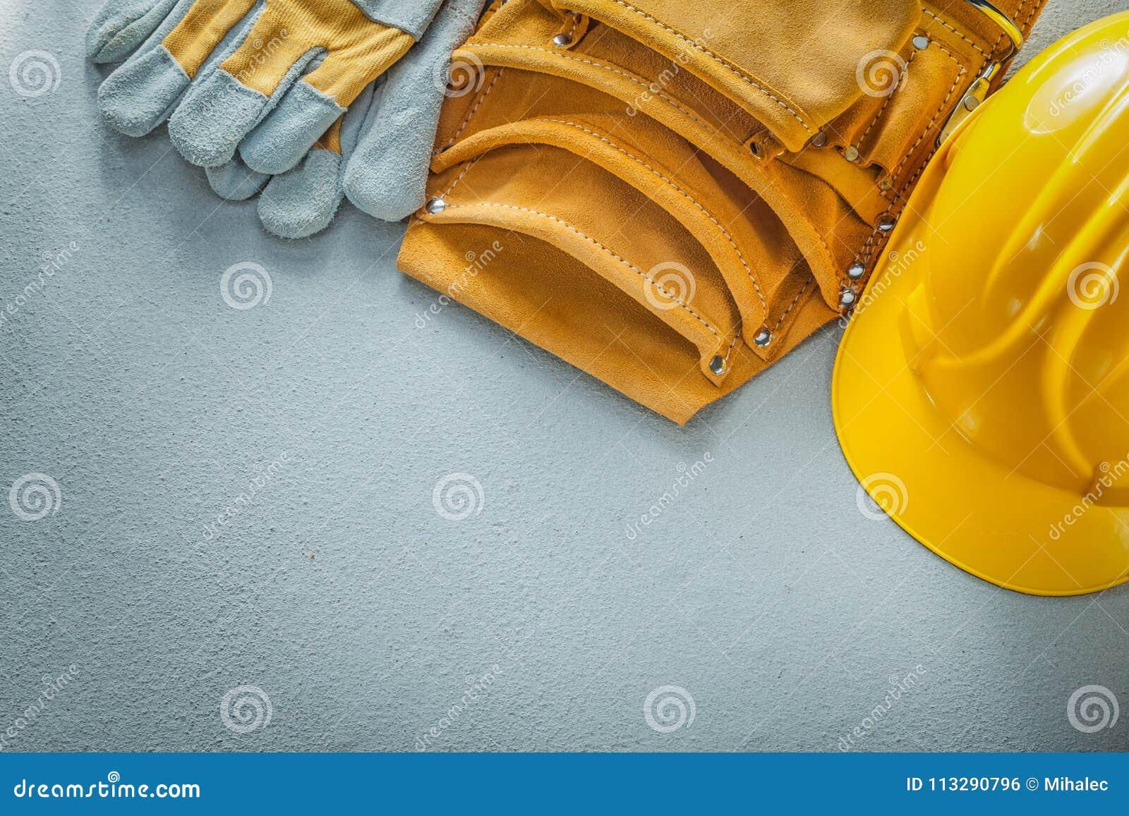 Equipe los guantes protectores de la correa que construyen el casco en backgrou concreto