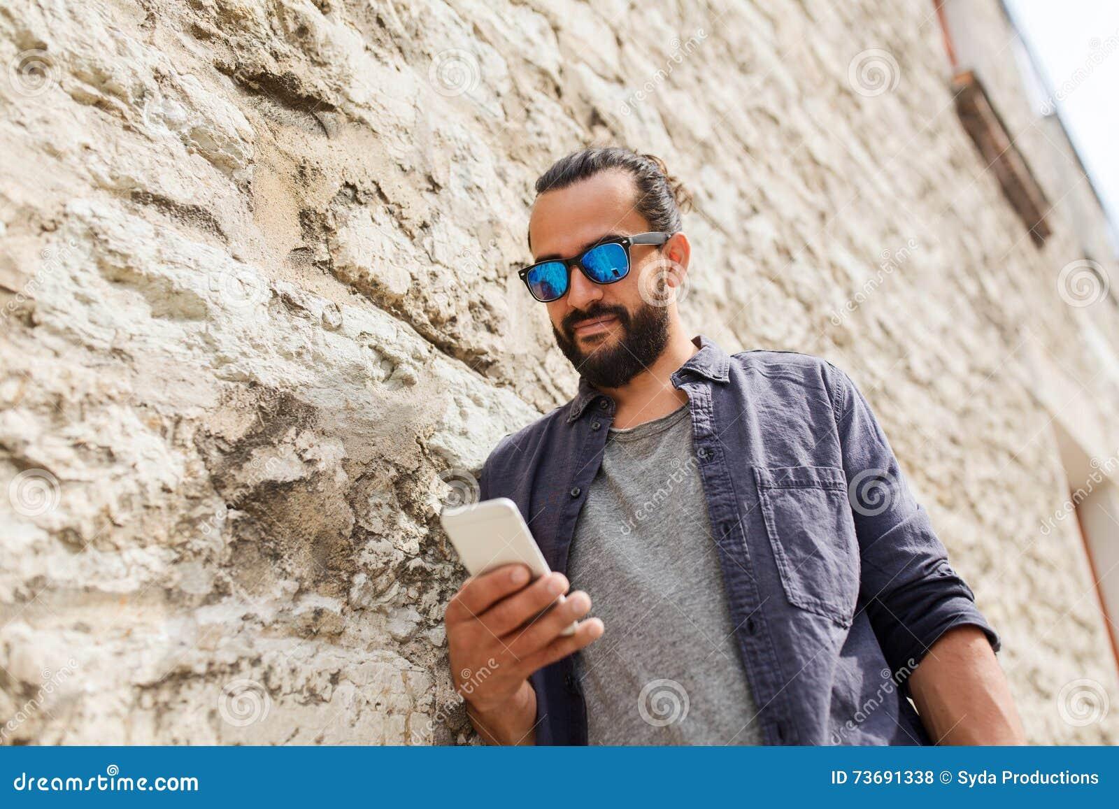 Lazer, tecnologia, comunicação e conceito dos povos - homem nos óculos de  sol que texting a mensagem no smartphone na parede de pedra e125d512d6