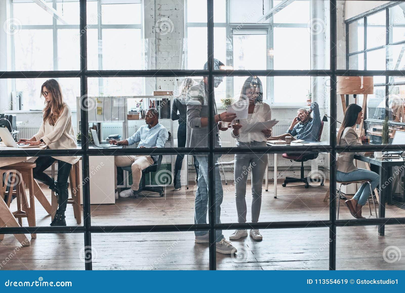 Equipe no trabalho Comprimento completo do trabalho moderno novo dos povos e da COM