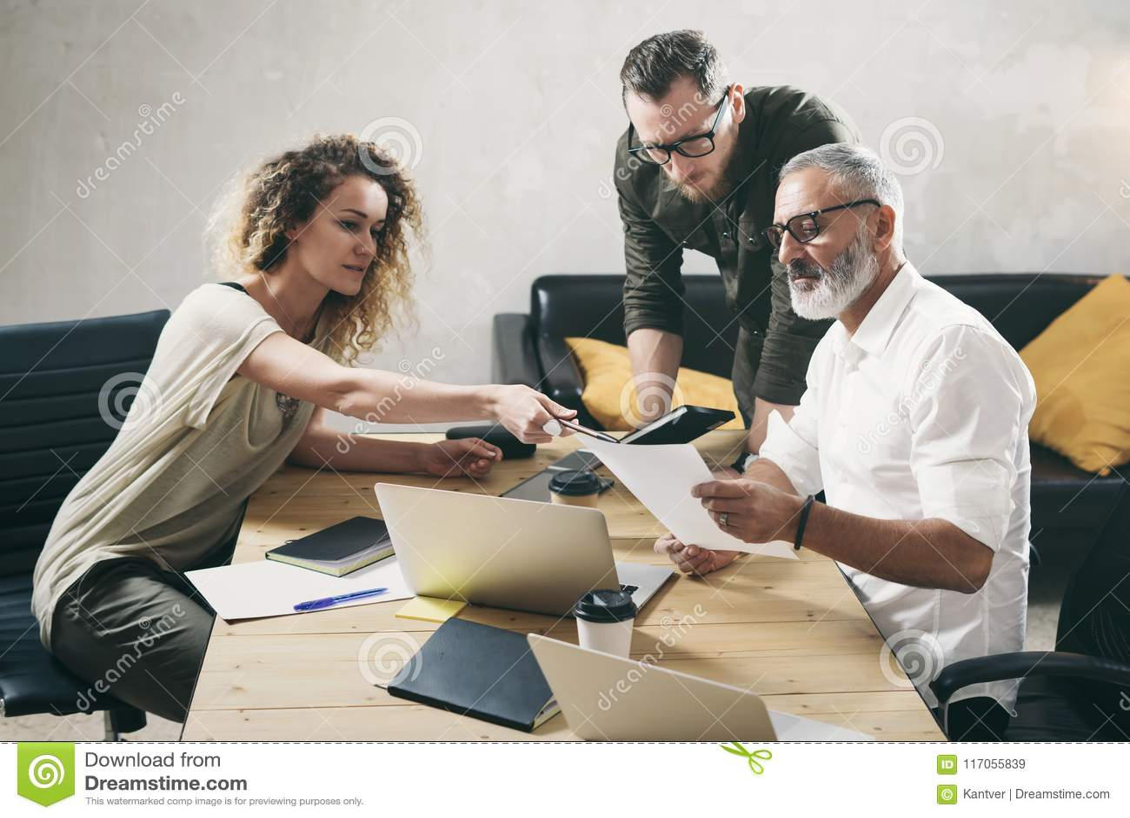 Equipe nova dos colegas de trabalho que fazem a grande discussão do trabalho no escritório moderno Homem farpado que fala com dir