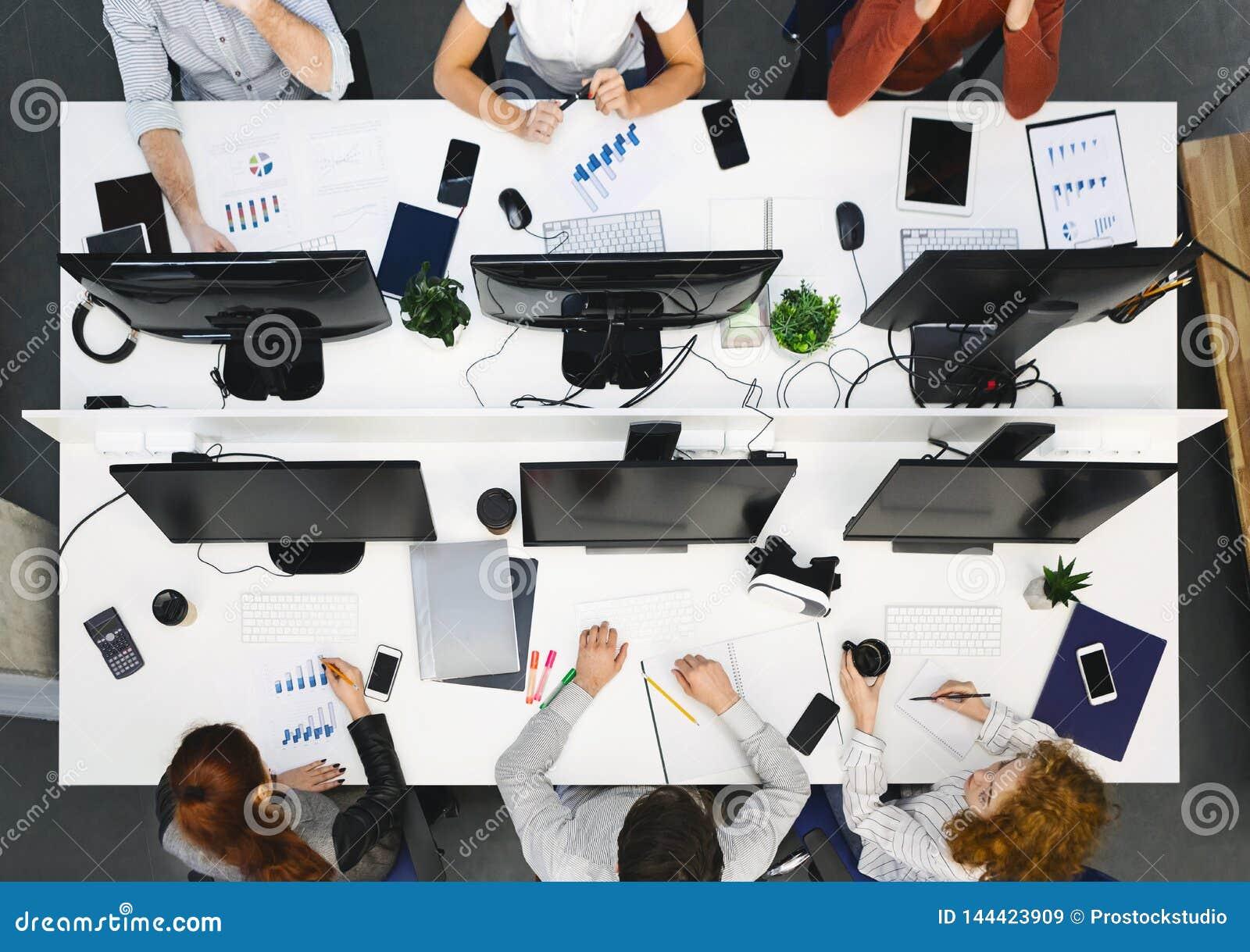 Equipe nova que trabalha em computadores no escritório moderno