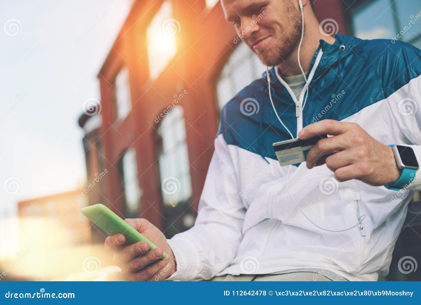 Equipe o assento fora com cartão e telefone celular de crédito, Internet banking e compra em linha