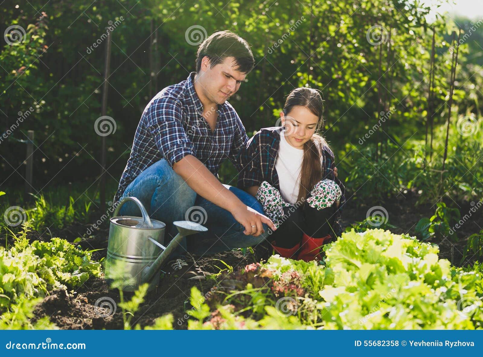 Equipe o assento no jardim com filha e o ensino lhe do horticultur