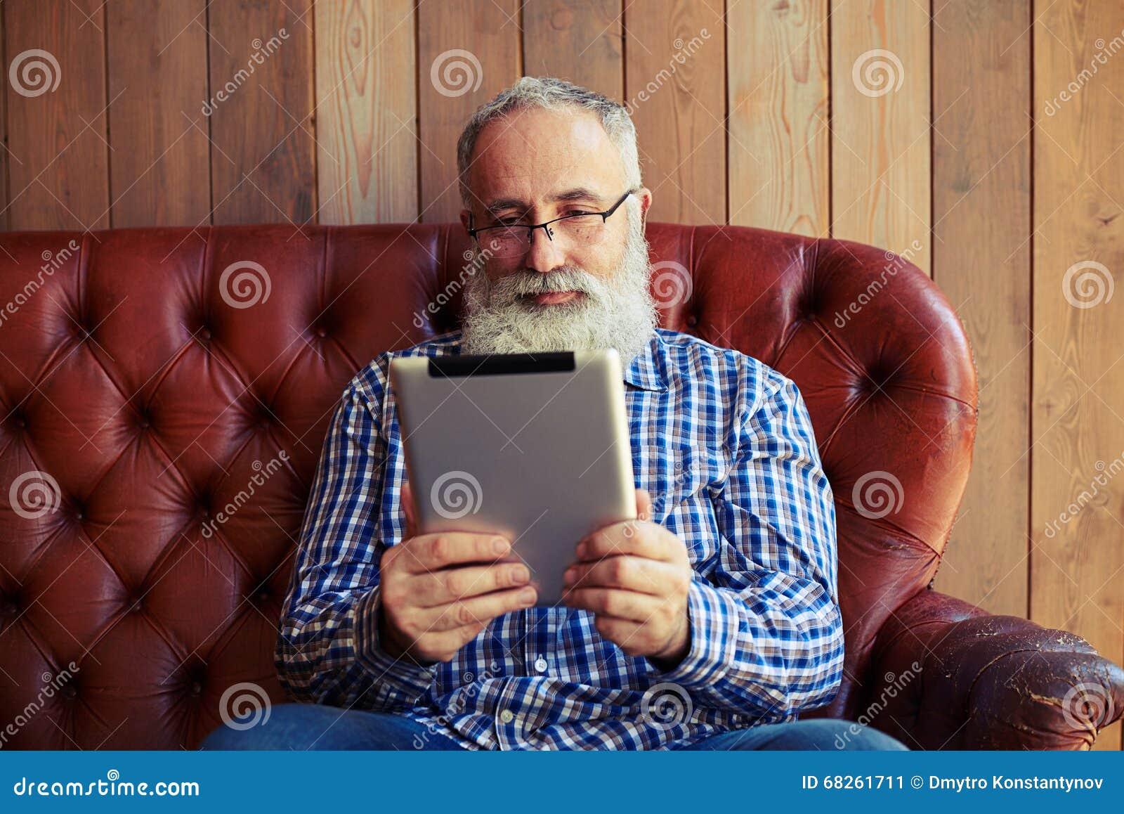 Equipe o assento no sofá e a leitura da notícia em seu PC da tabuleta