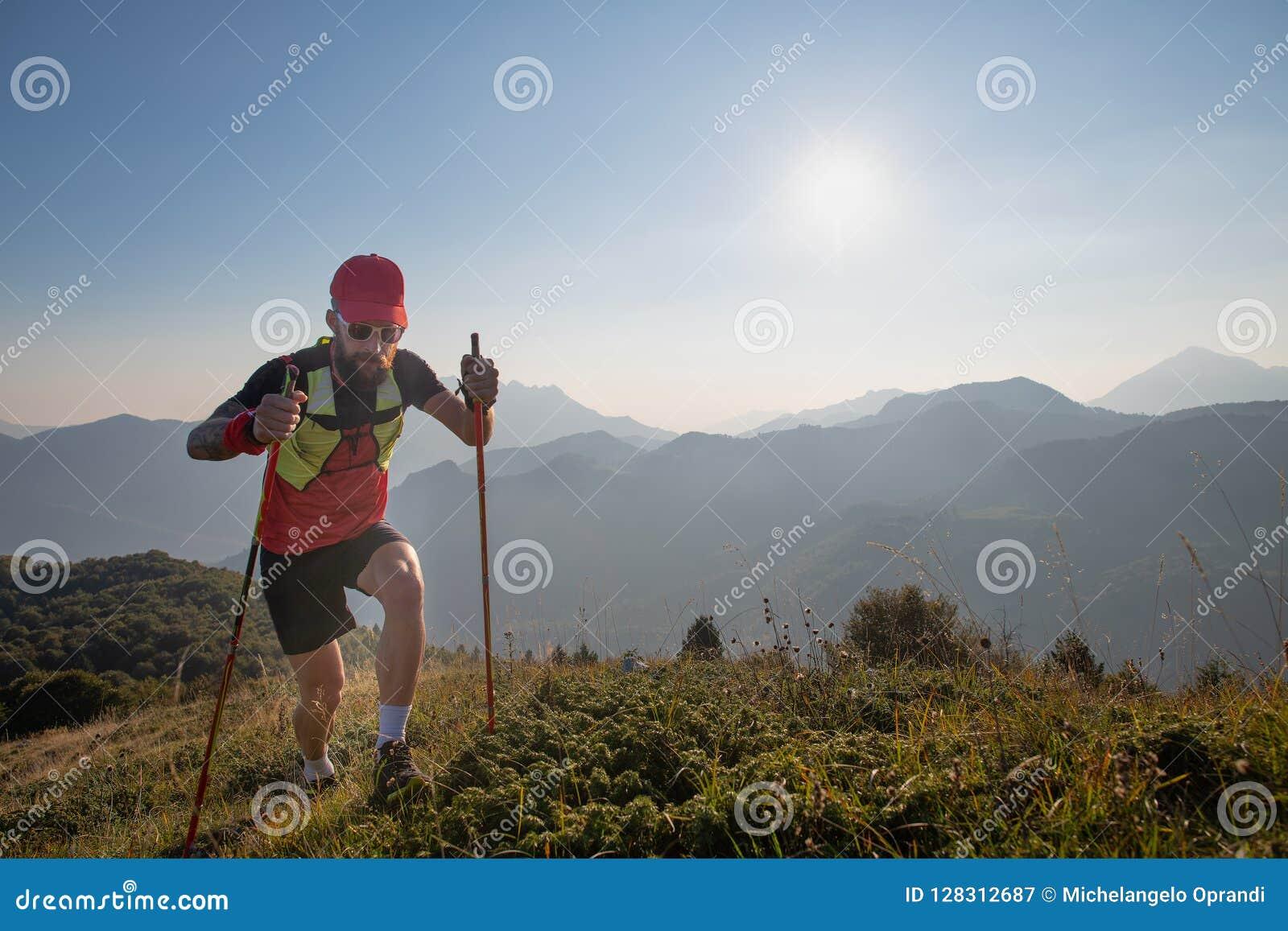 Equipe o atleta da céu-invasão nas montanhas com as varas dos polos subida