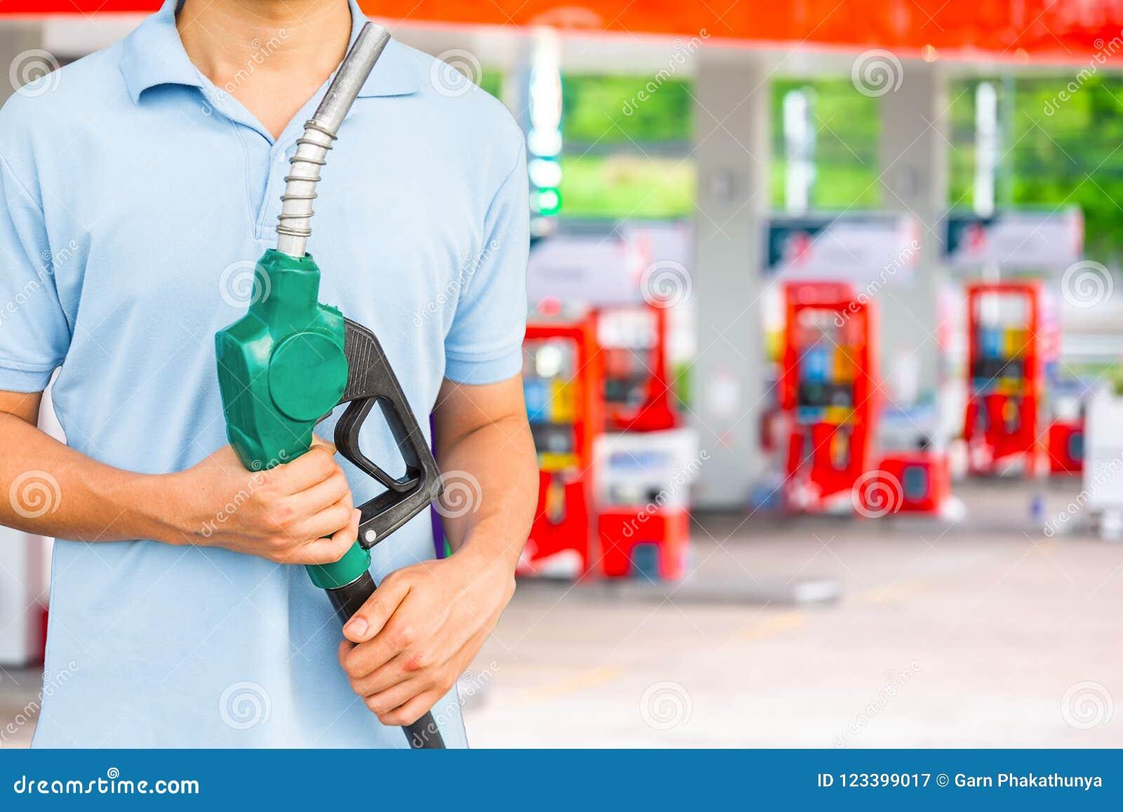Equipe o bocal de combustível da posse para adicionar o combustível no carro no posto de gasolina