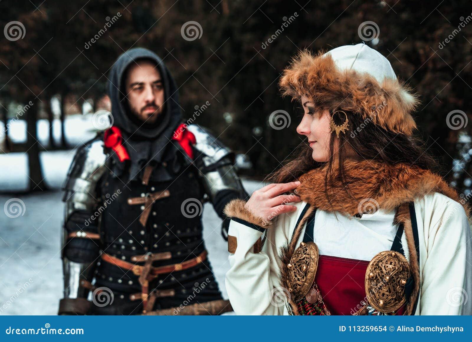 Equipe o cavaleiro na armadura e na mulher no traje histórico